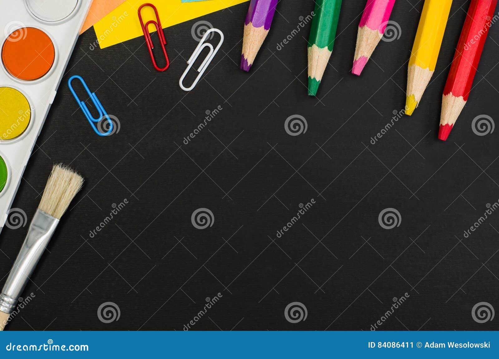 Школьные принадлежности граничат на черной предпосылке доски Фотоснимок взгляд сверху