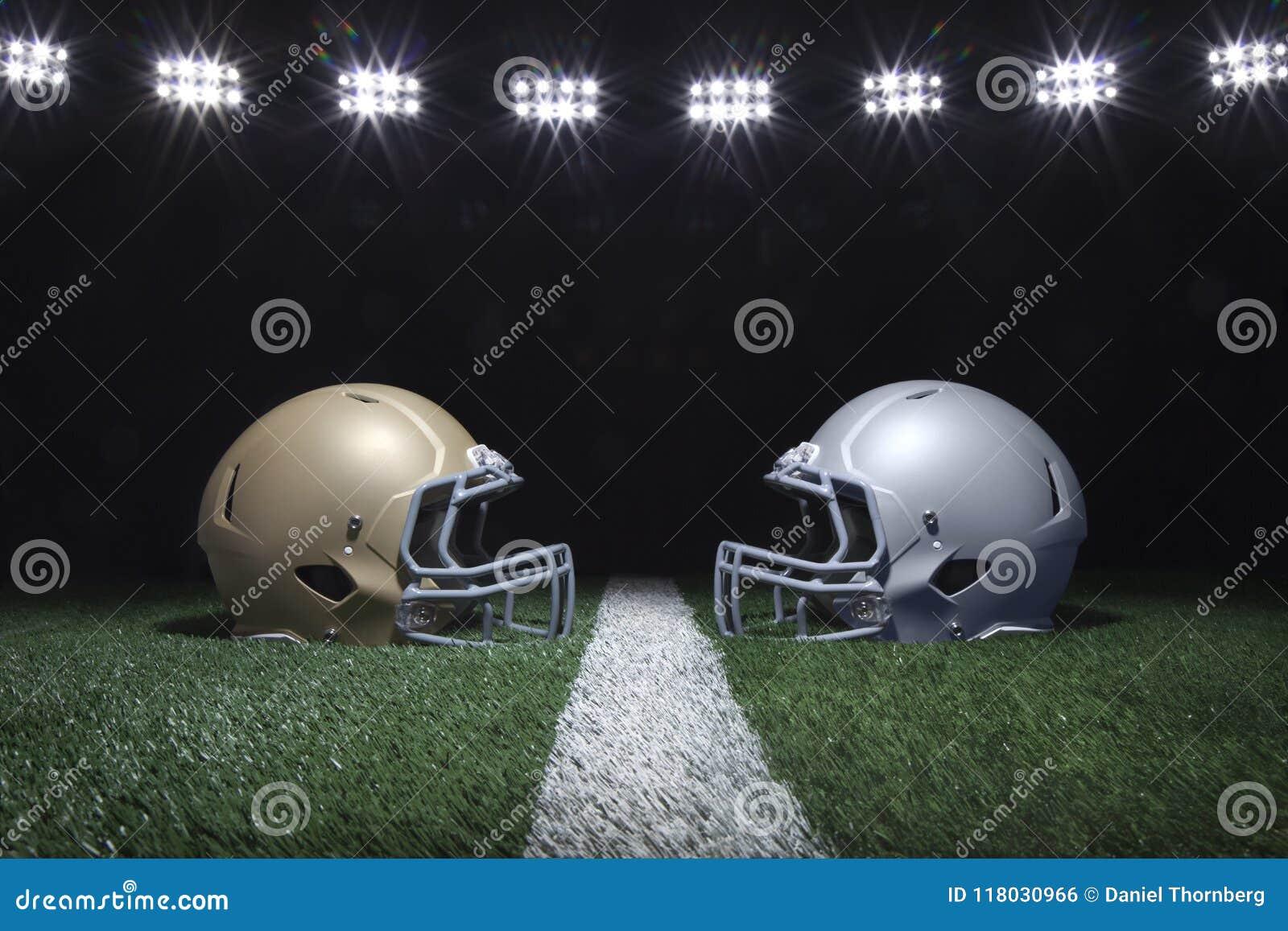 Шлемы футбола смотря на на линии разметки поля под стадионом освещают