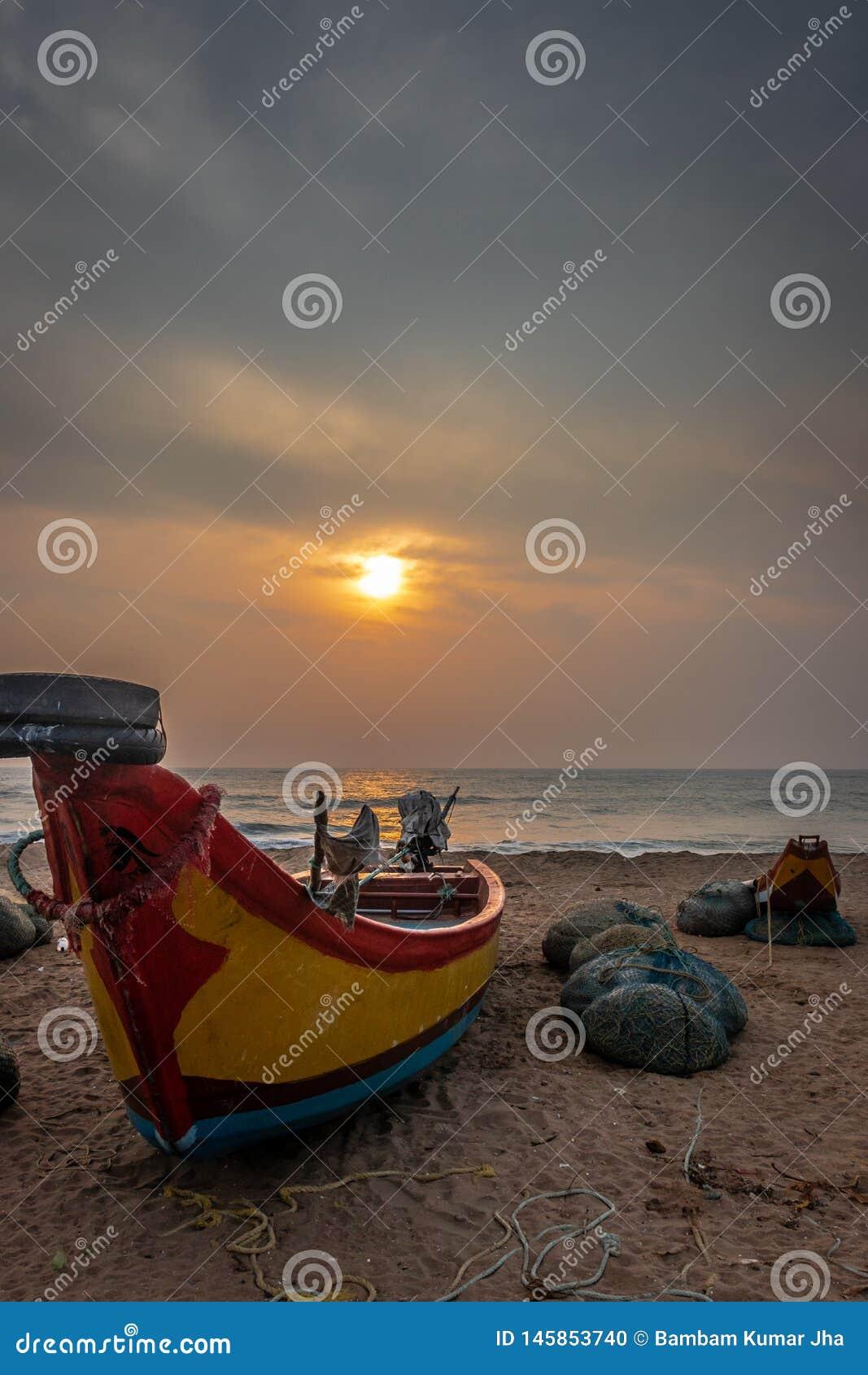 Шлюпка рыболовов на взгляде восхода солнца берега