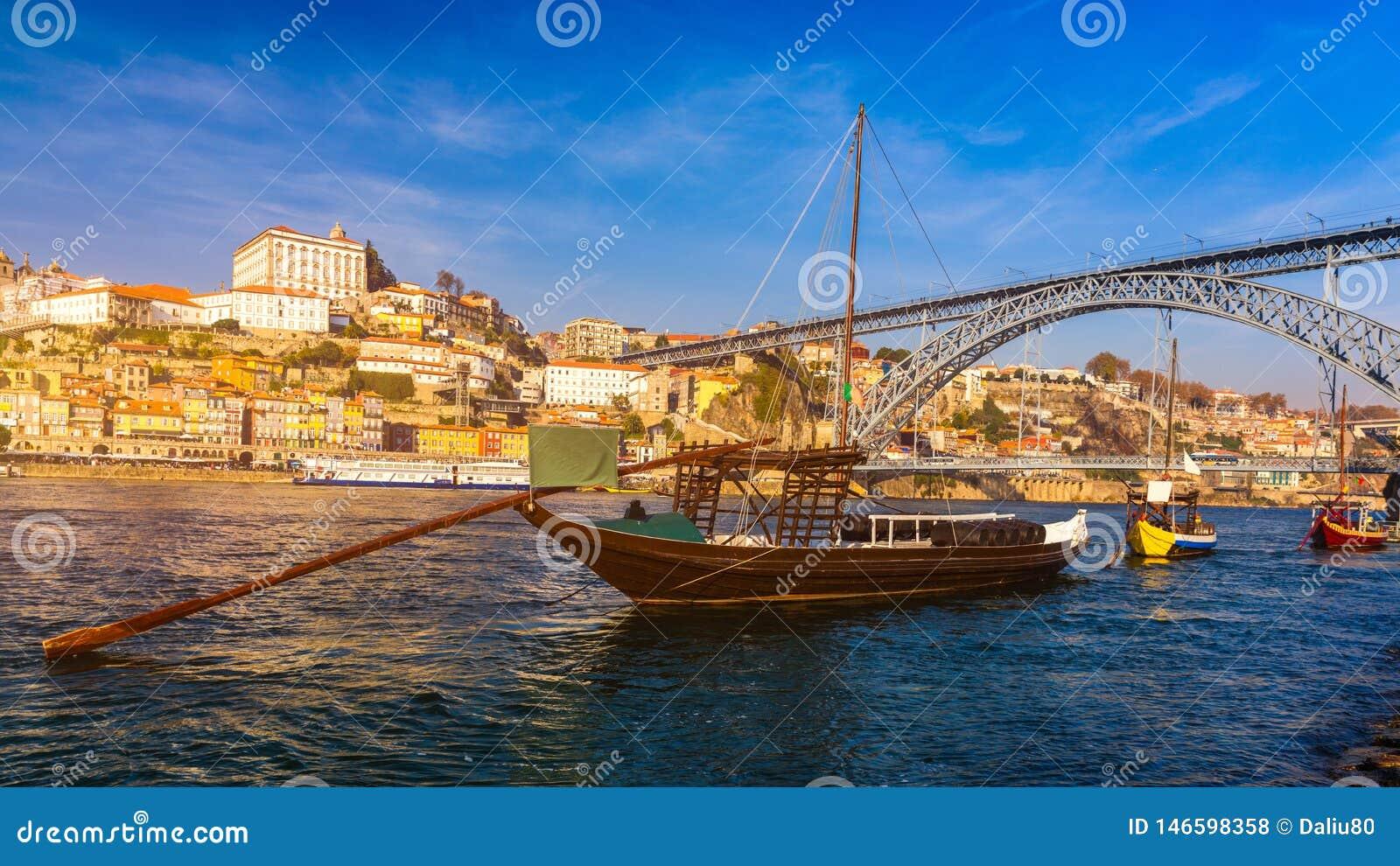 Шлюпки вина гавани на портовом районе с мостом Dom Луис и старом городке на реке Дуэро в Ribeira в центре города Порту