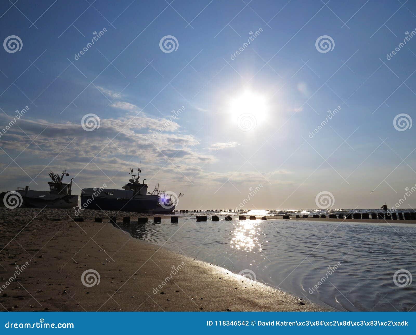 Шлюпки рыболова на взморье песчаного пляжа в Солнце