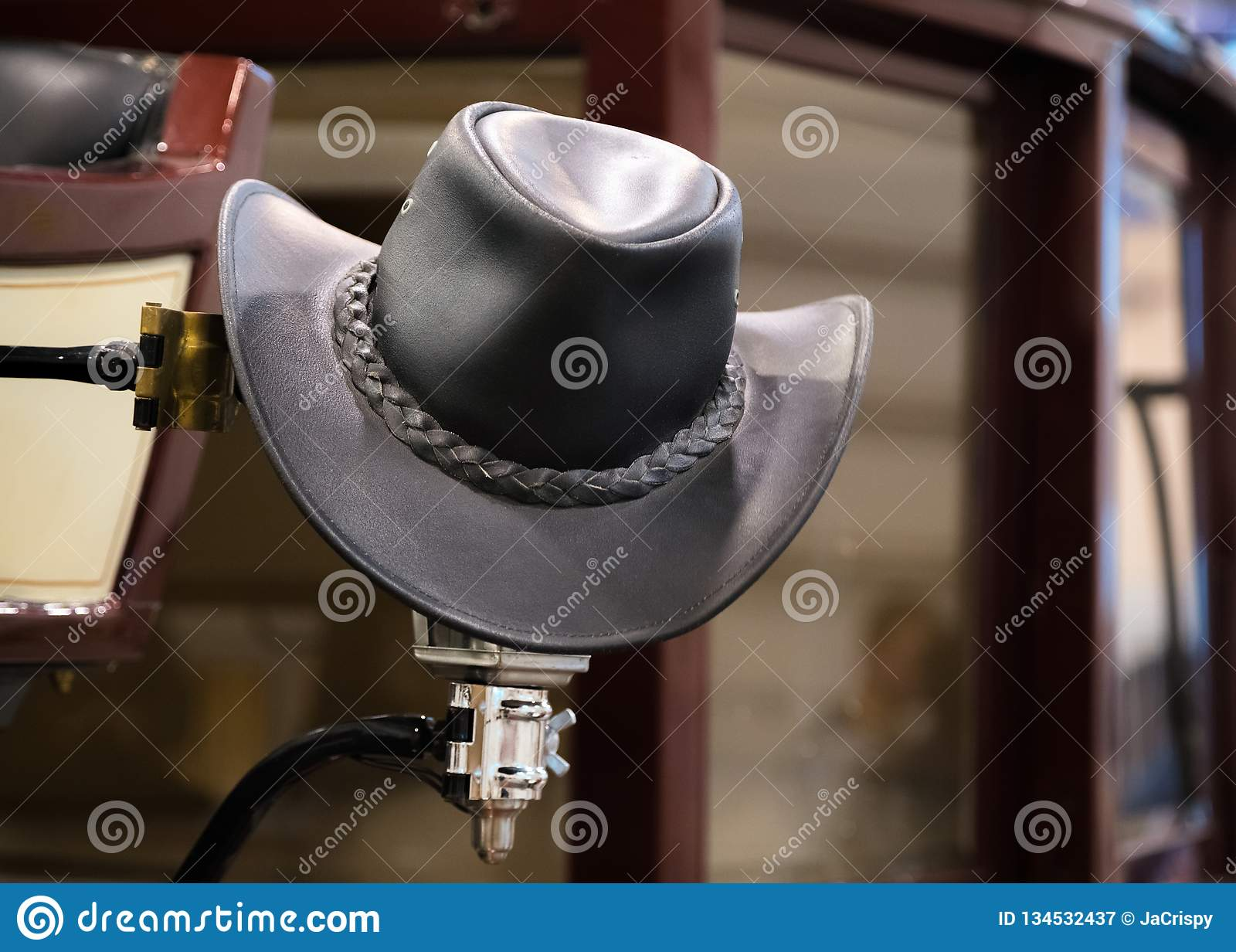Шляпа американского западного ковбоя родео черная кожаная в старом деревянном амбаре ранчо