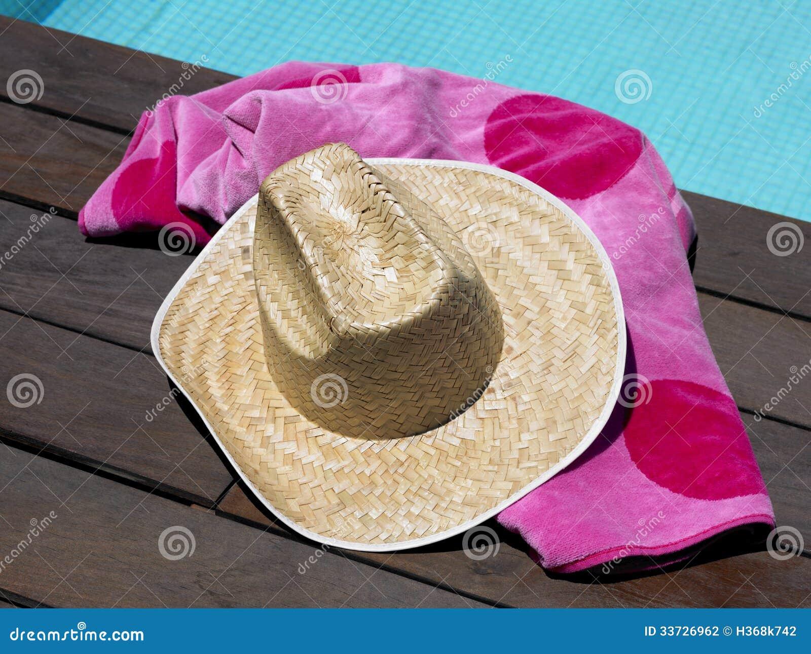 Шляпа и пляжный полотенце Солнця бассейном