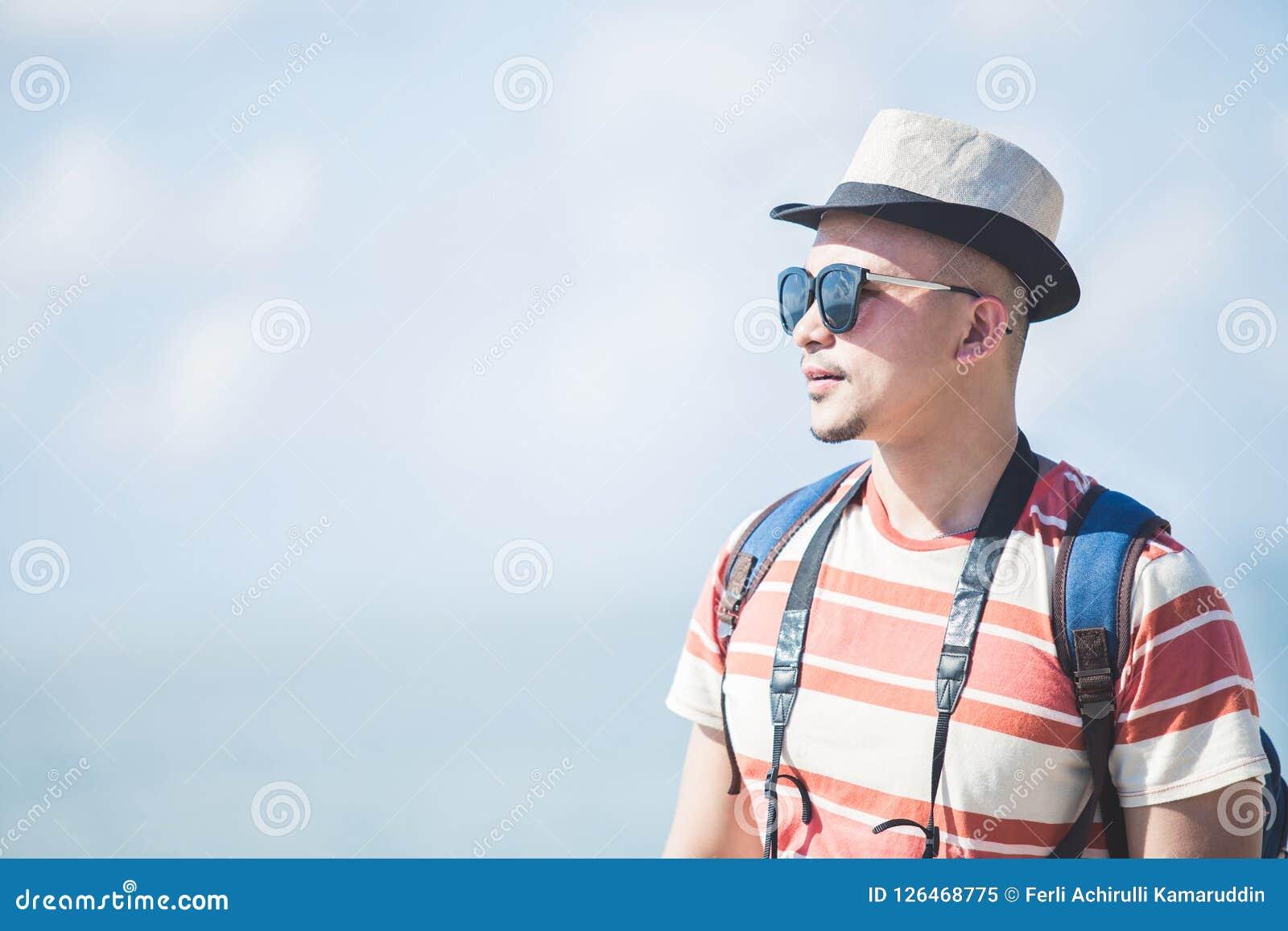 Шляпа и солнечные очки лета сольного путешественника нося во время каникул