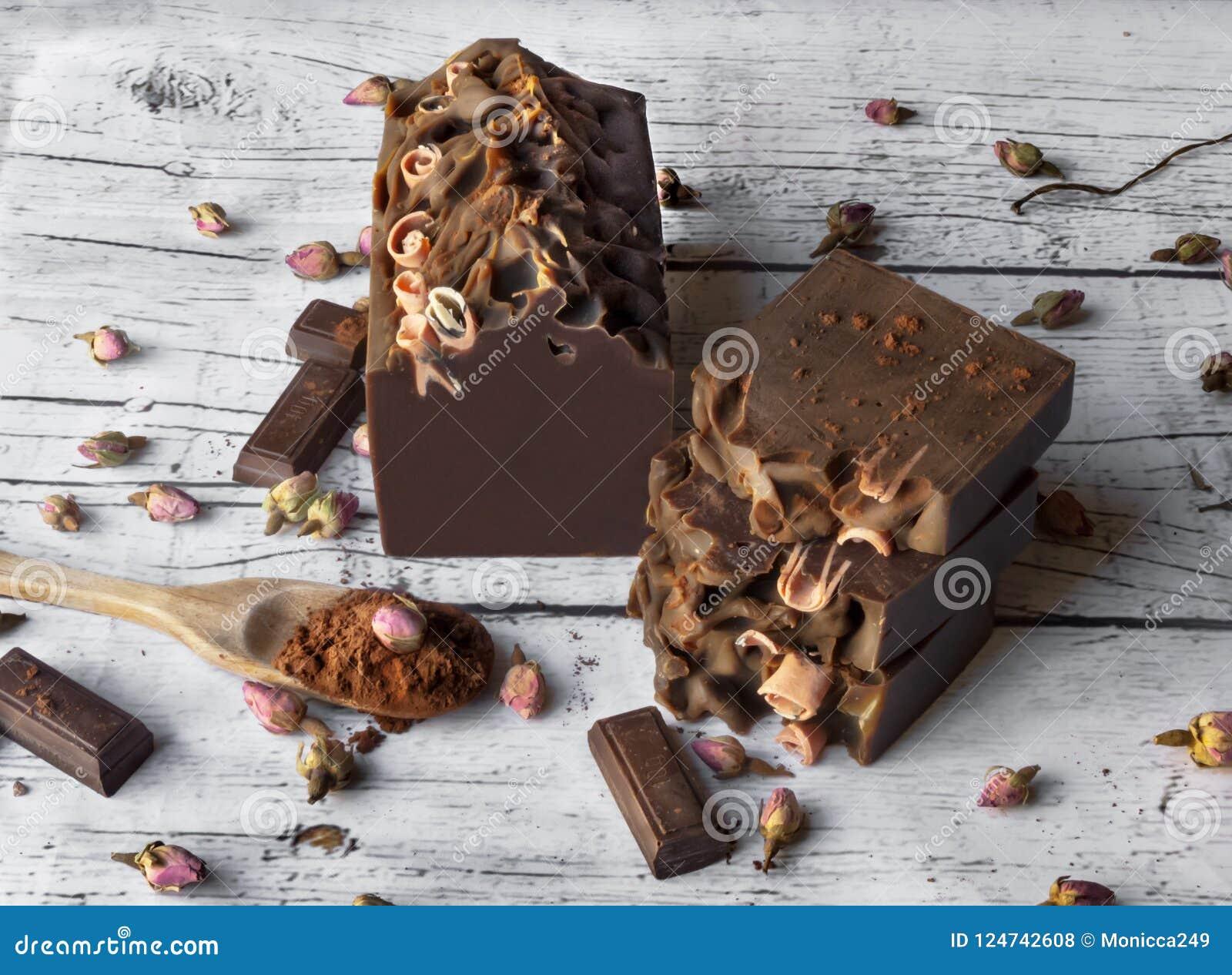 Шоколад и мыло бара роз на белой деревянной предпосылке