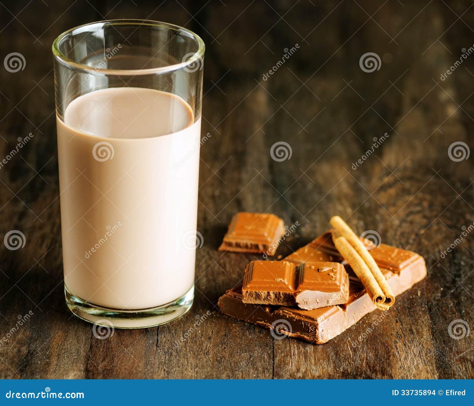 Шоколадное молоко с шоколадом и циннамоном на темном деревянном столе