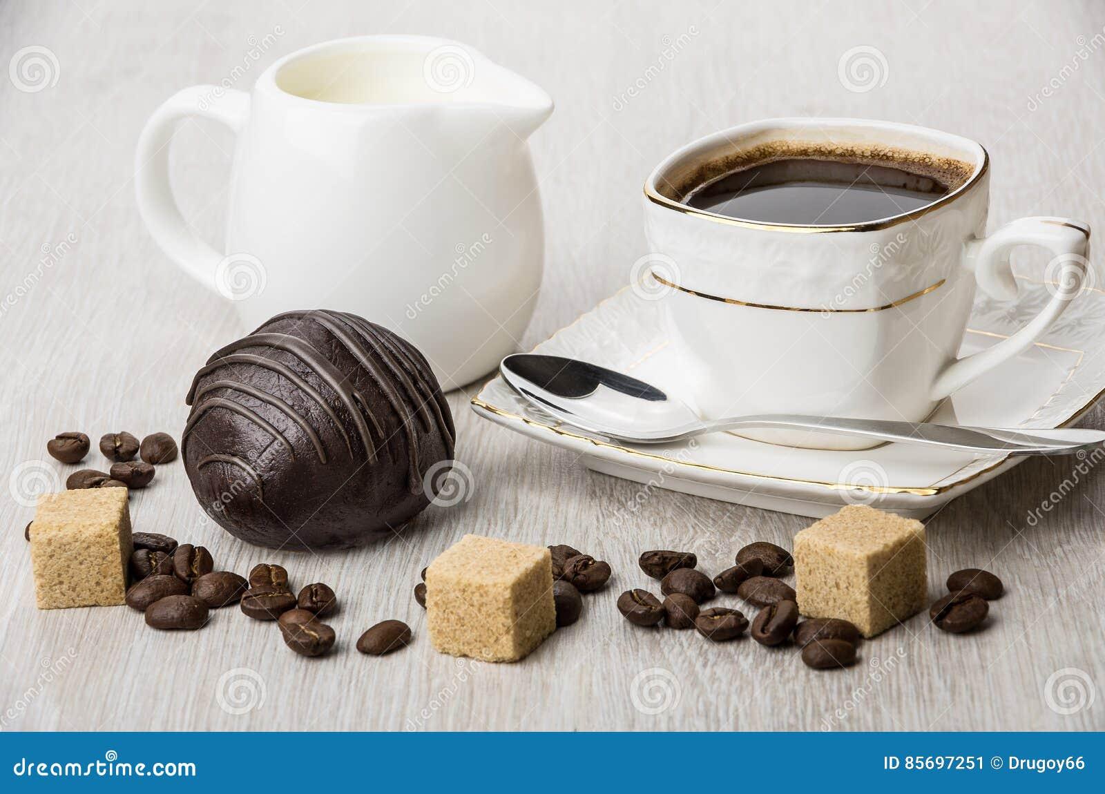 Шоколадный торт, молоко кувшина, части сахара и кофейная чашка