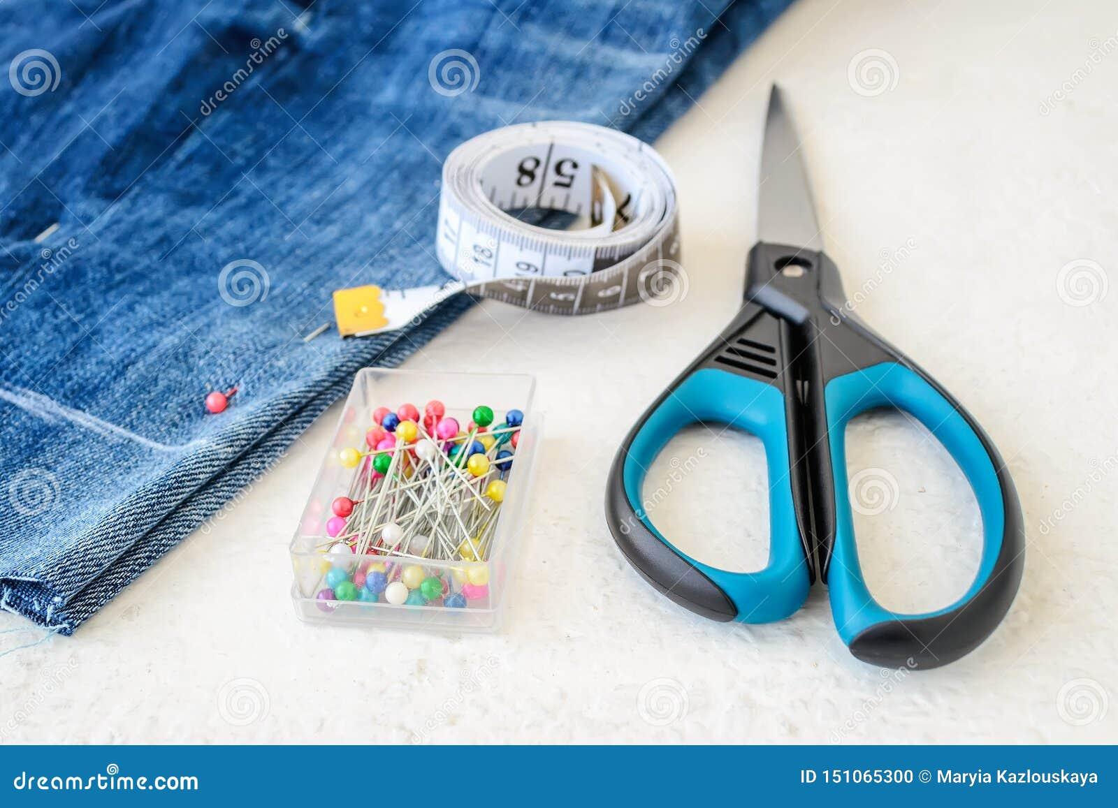 Шорты голубых джинсов, крен покрашенной ленты портноя с сантиметрами и дюймы, multi возглавили шить штыри в коробке и ножницах