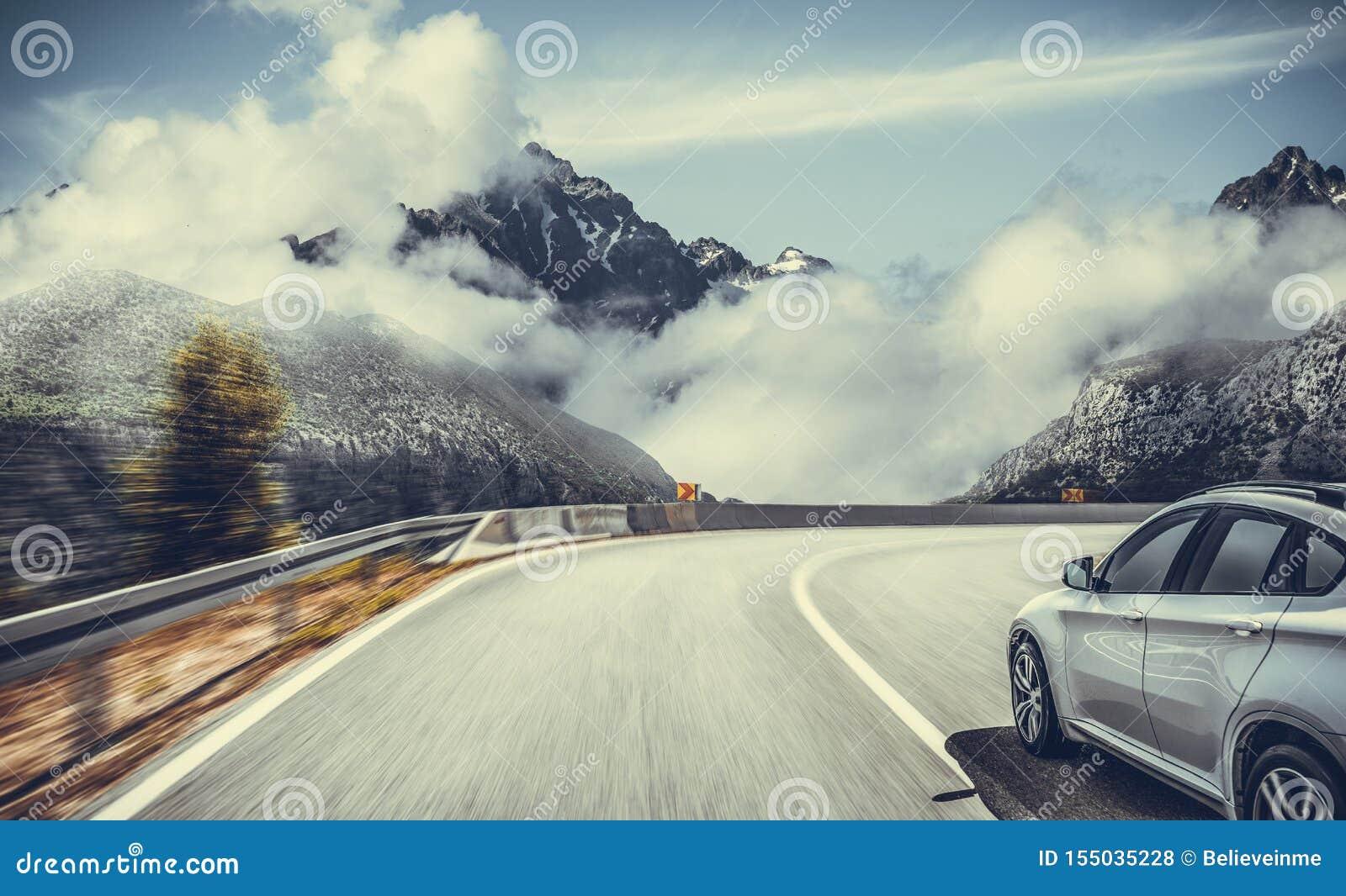 Шоссе среди пейзажа горы Белый автомобиль на дороге горы