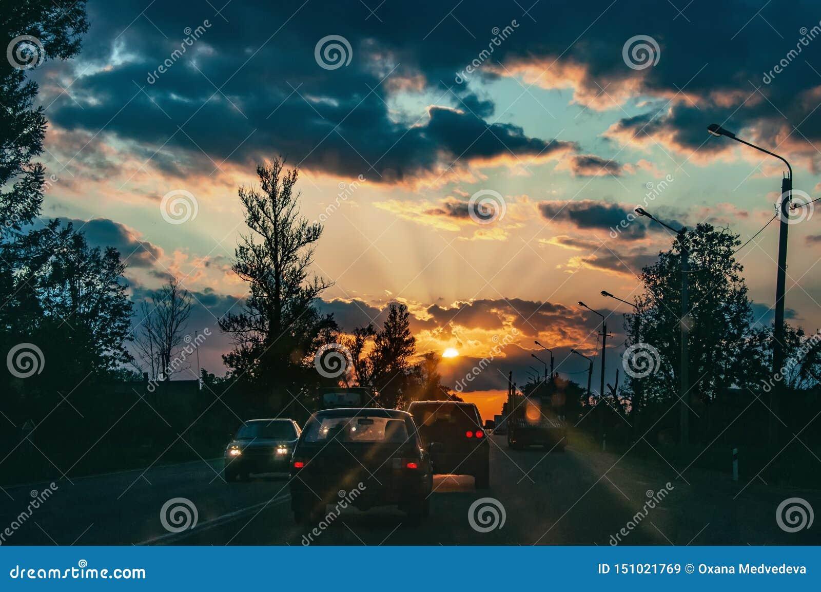 Шоссе с автомобилями путешествуя на заходе солнца Линия горизонта с солнцем и облаками шторма Путешествия r