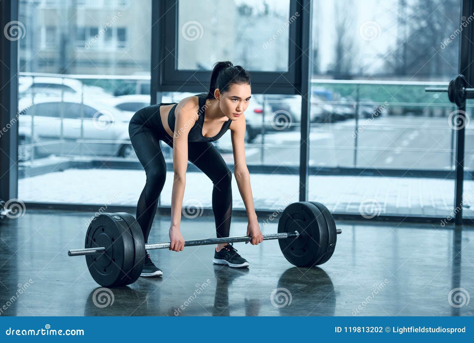 штанга молодой атлетической женщины поднимаясь