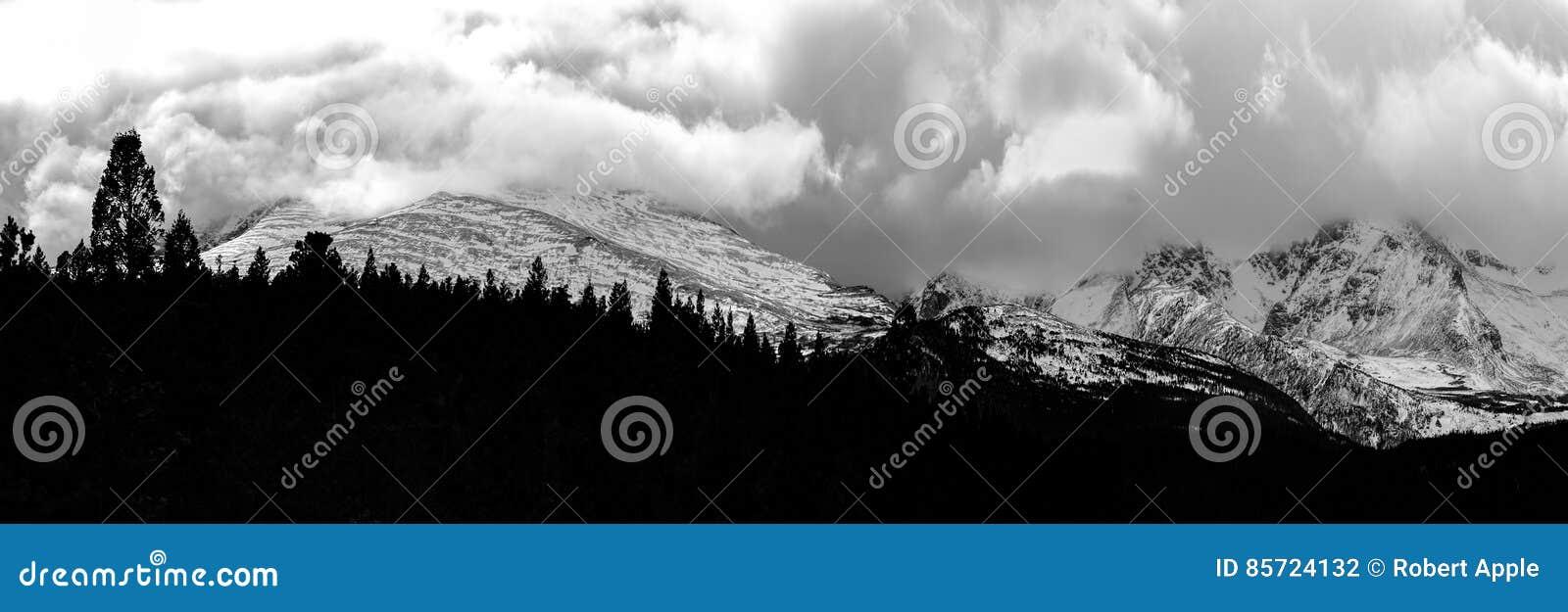 Шторм зимы заваривая над скалистыми горами