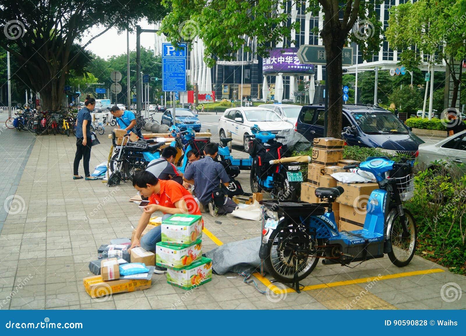 Шэньчжэнь, Китай: на компании курьера тротуара работники распределяют курьера клиента