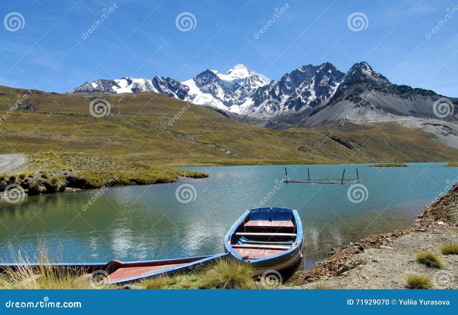 Шлюпка в снеге озера и горы выступает позади