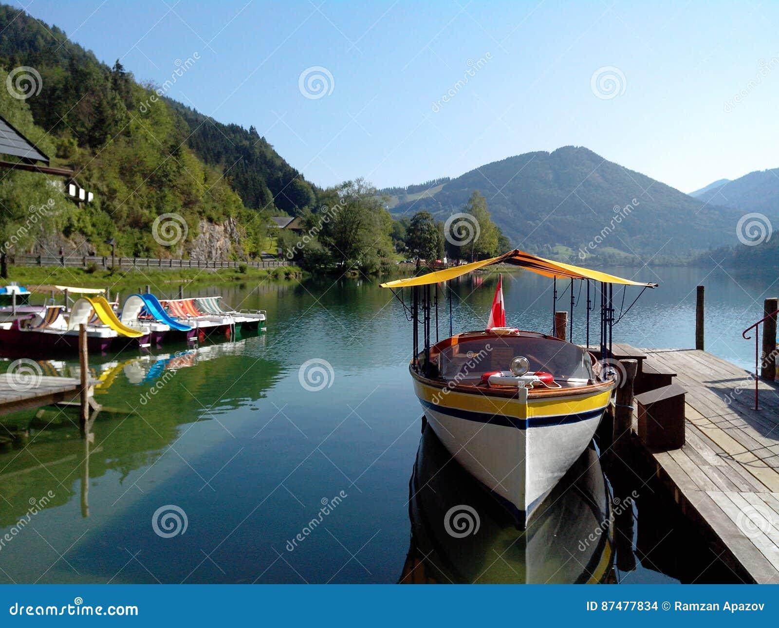 Шлюпка и катамараны на озере горы
