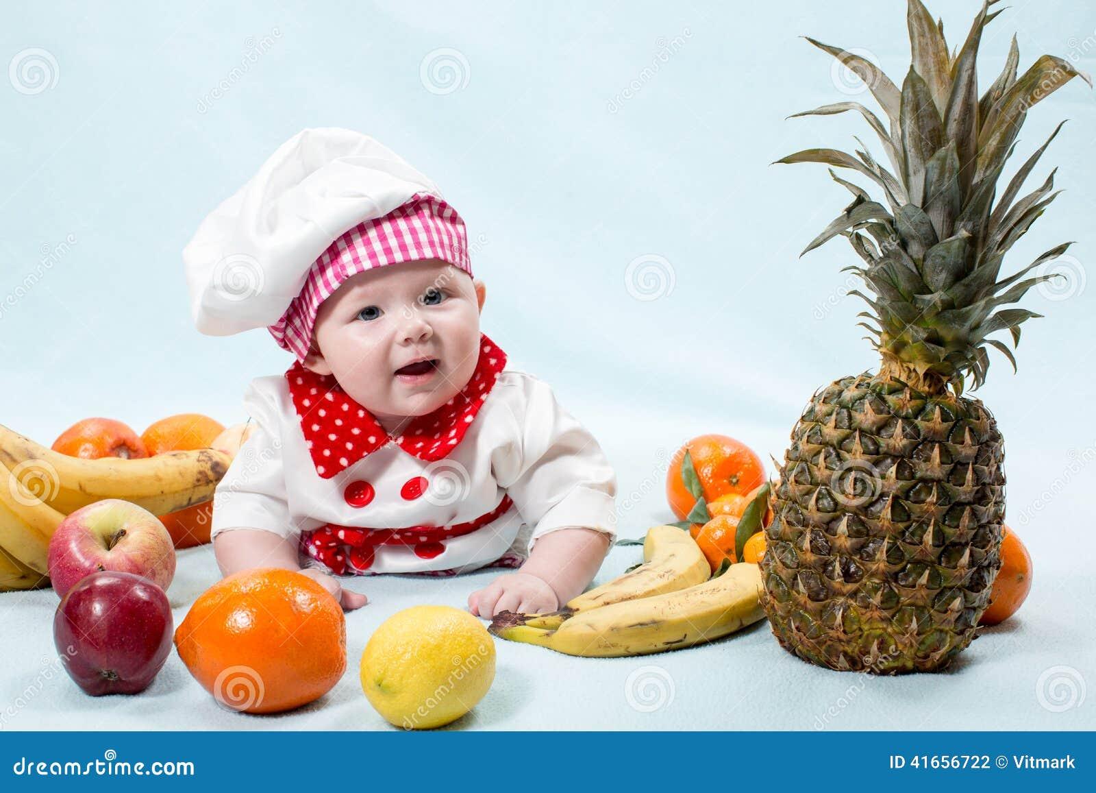 Шляпа шеф-повара девушки кашевара младенца нося с свежими фруктами