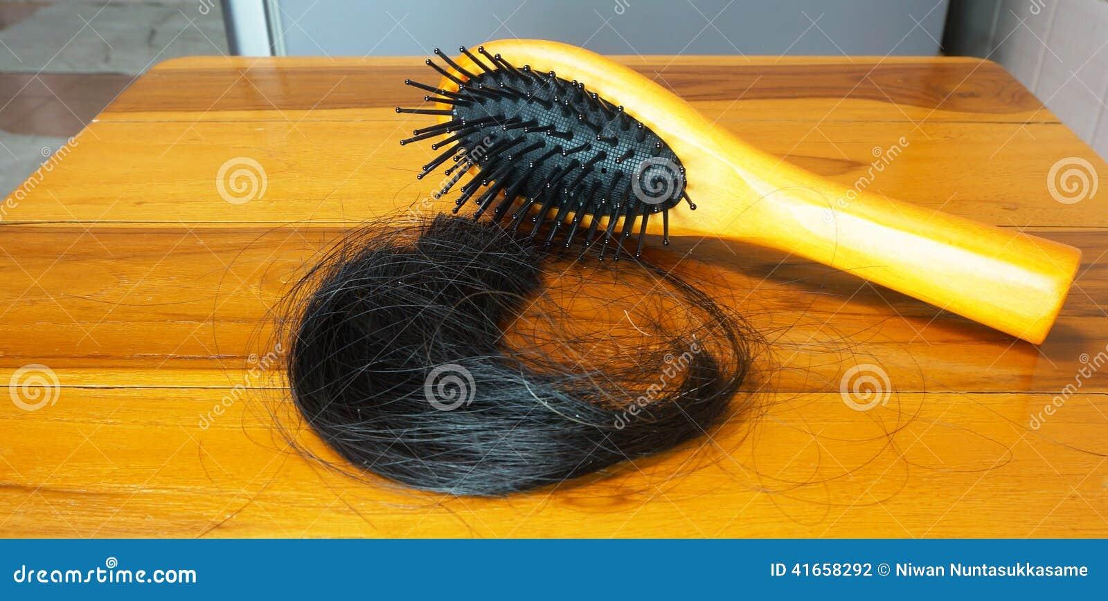 Щетка с потерянными волосами на деревянном столе