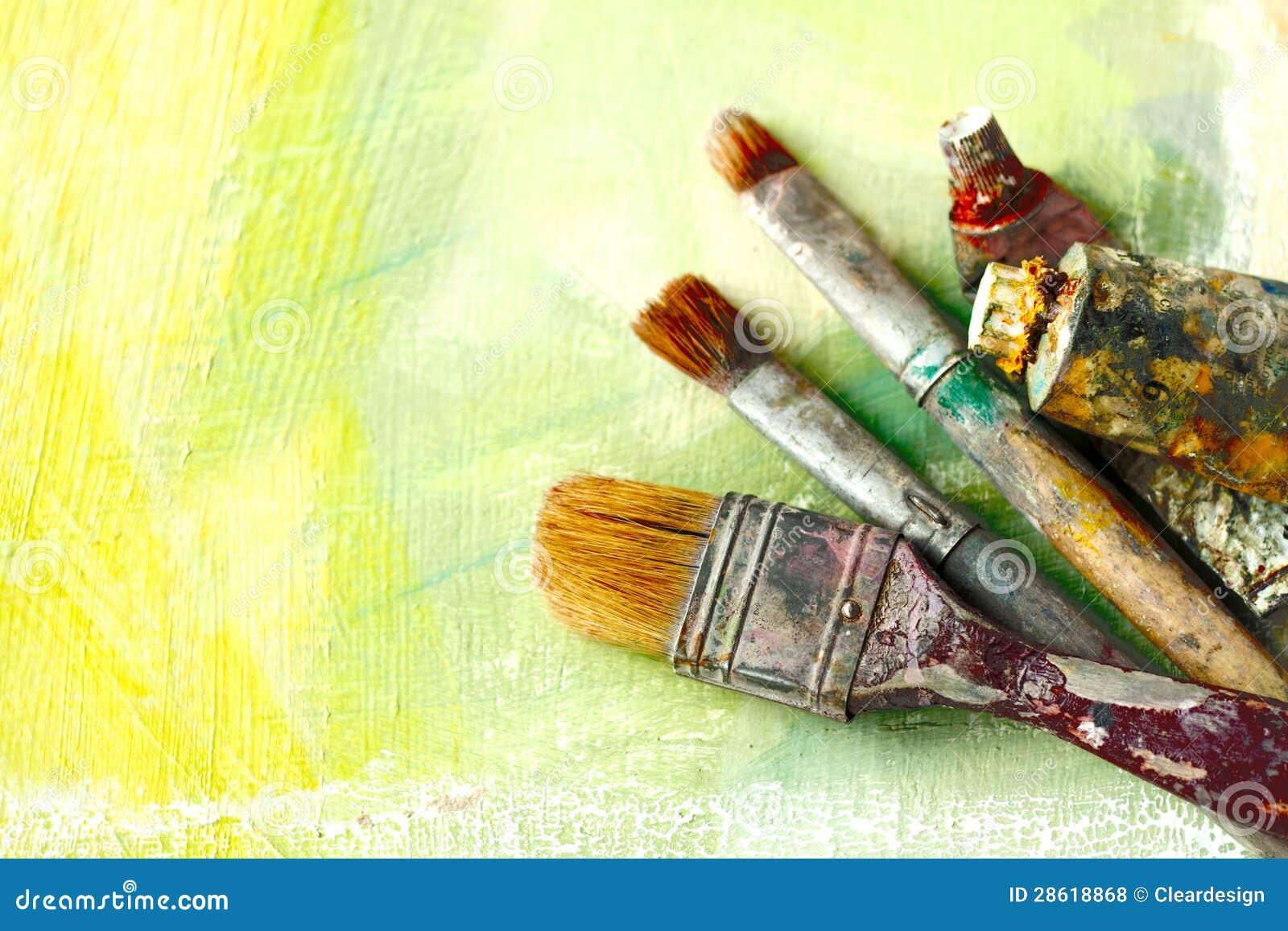 Щетки художников год сбора винограда и пробки краски на абстрактной художнической предпосылке