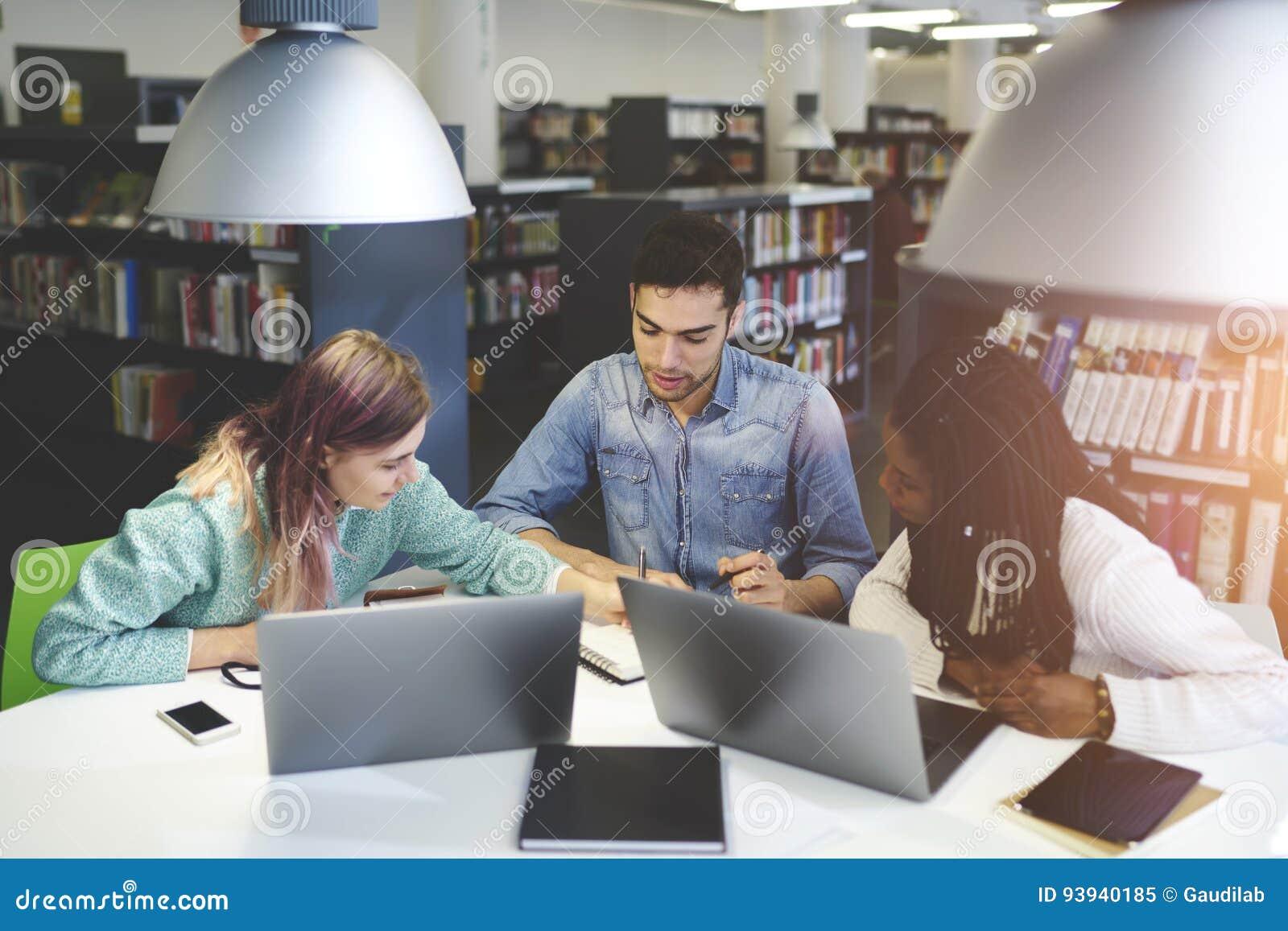 Экипаж умелого мужчины и женских международных студентов уча совместно
