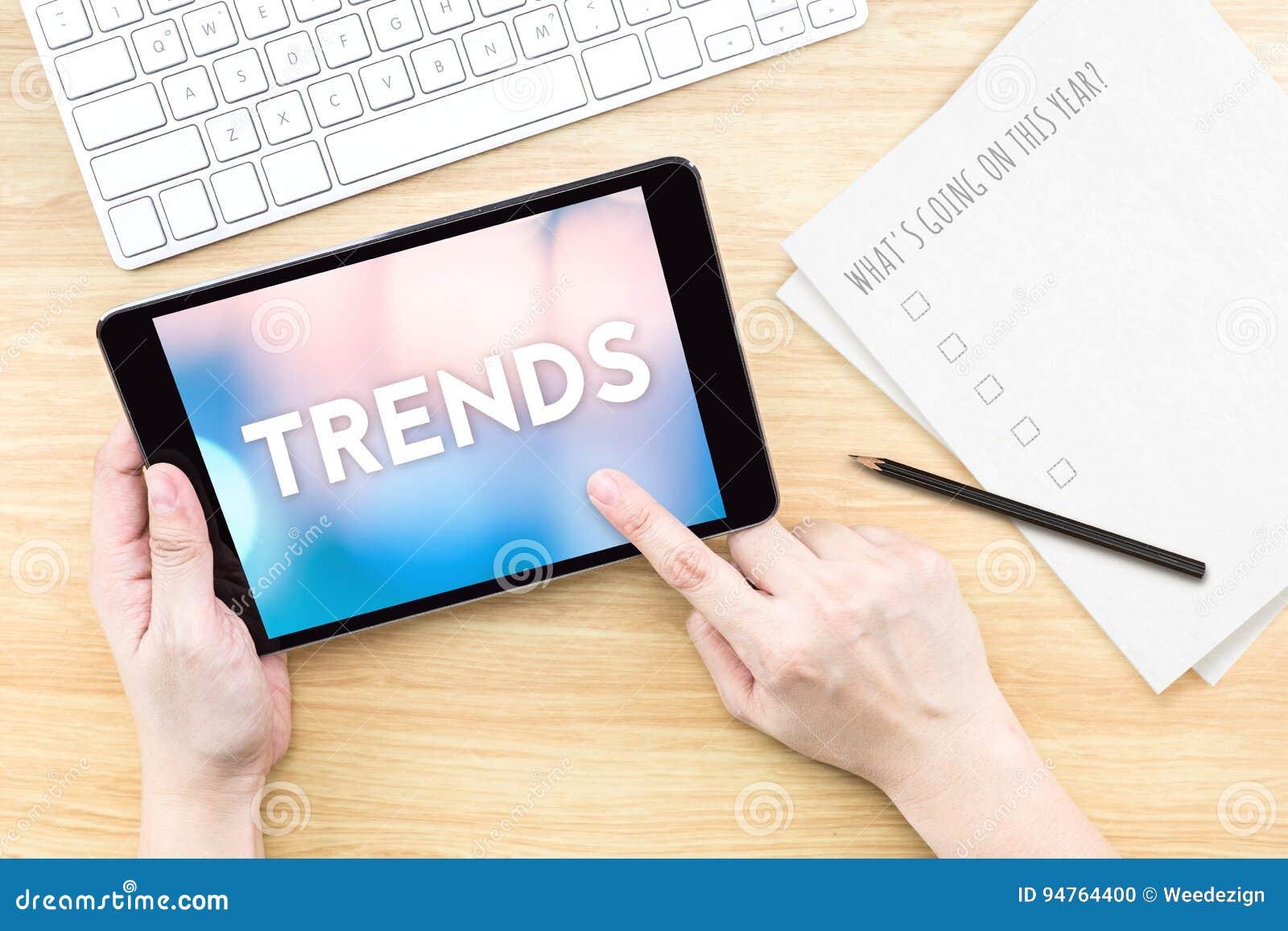 Экран касания пальца с словом тенденций с клавиатурой и бумагой дальше