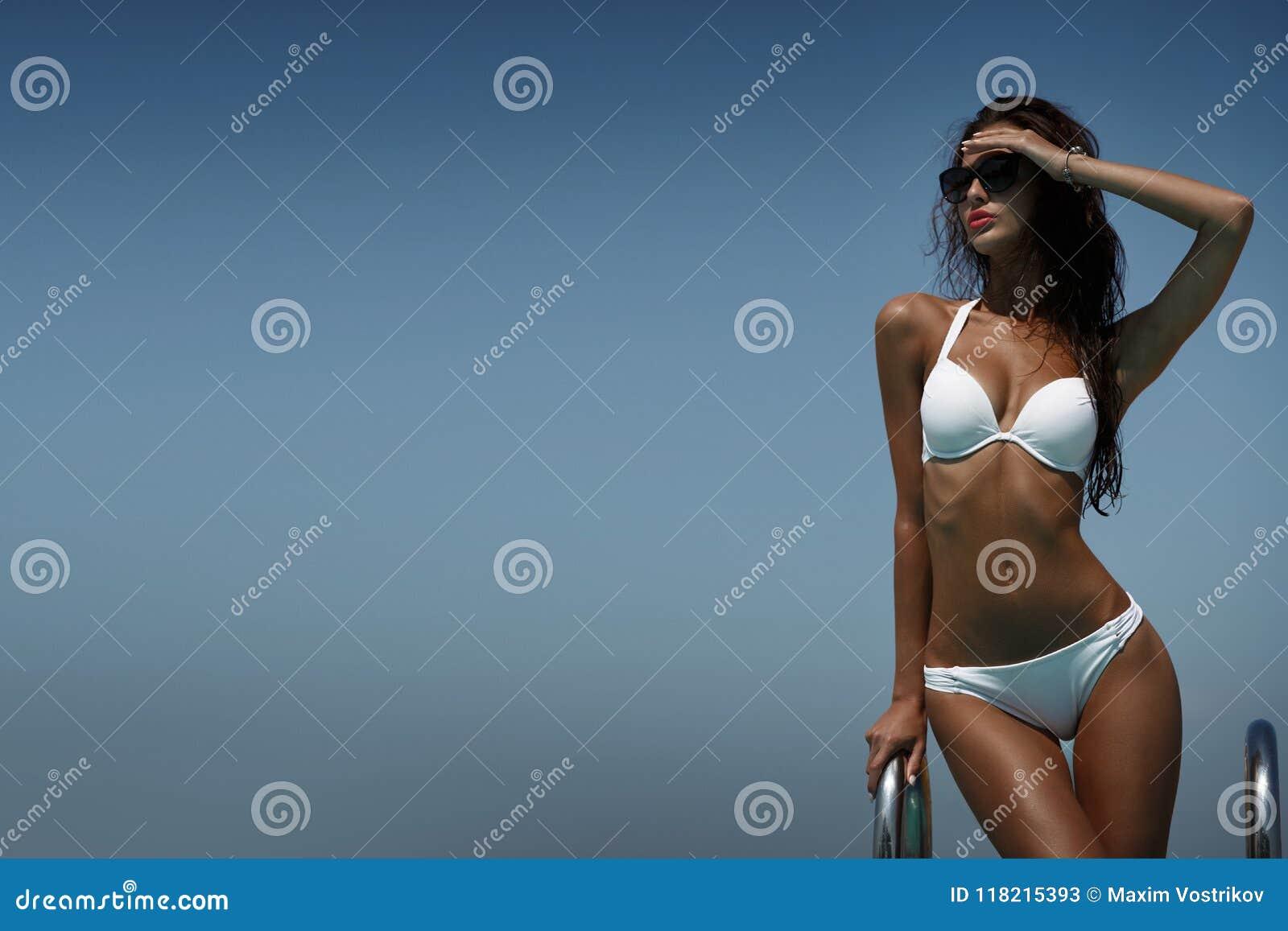 Элегантная женщина в белом бикини на солнц-загоренном тонком теле представляет около бассейна в хорошей жаркой погоде
