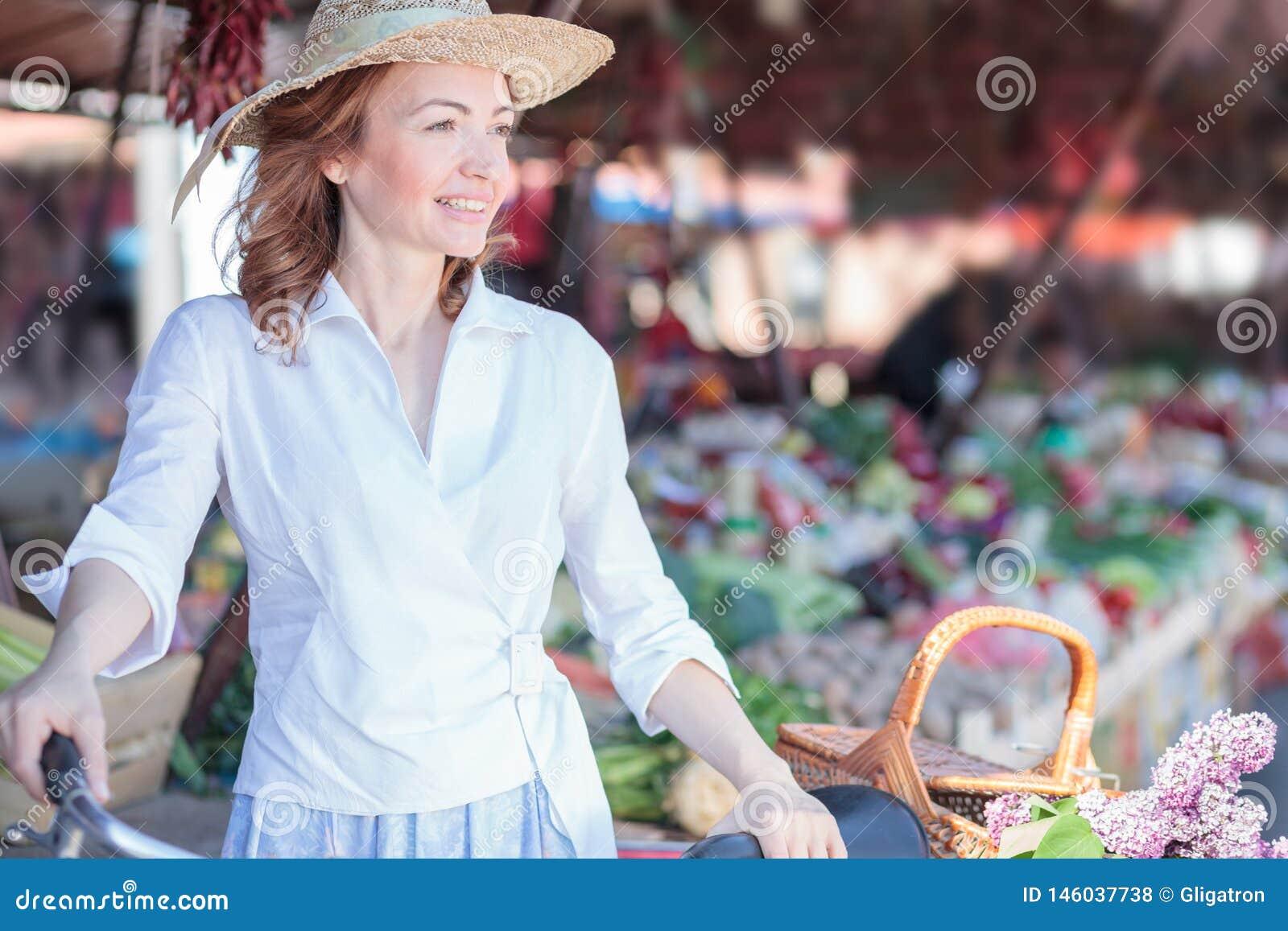 Элегантная зрелая женщина идя через под открытым небом рынок, ходя по магазинам для бакалей