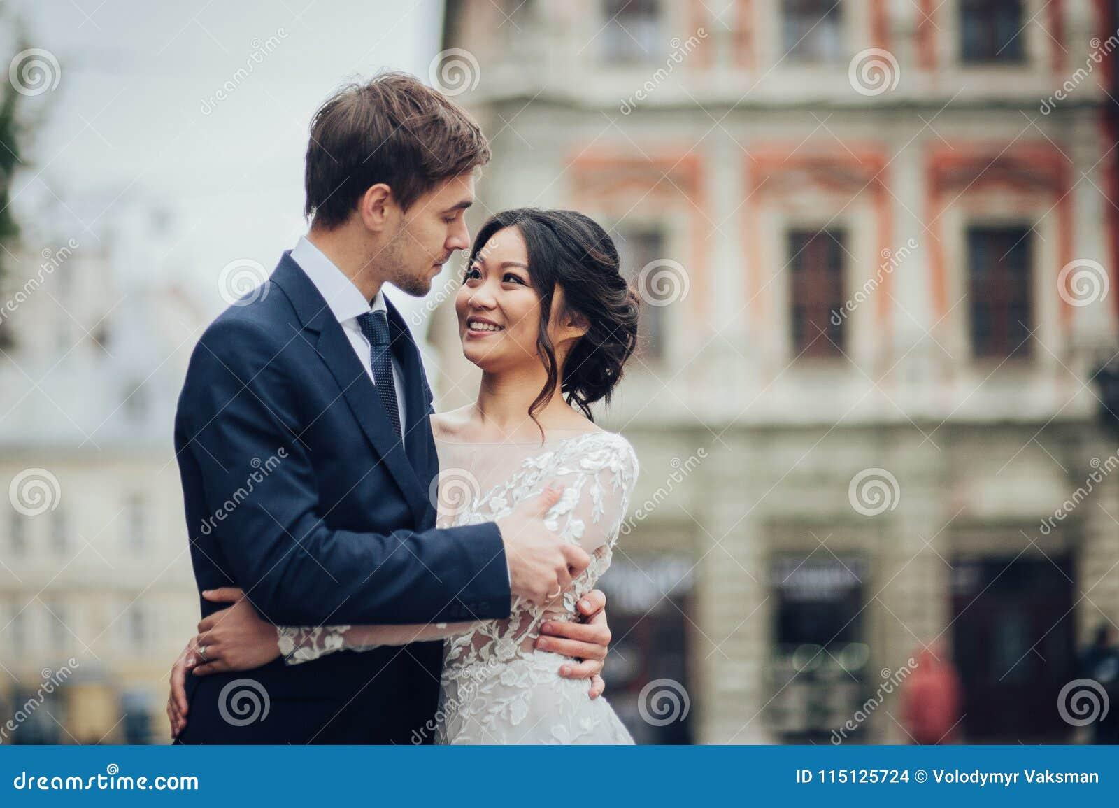 Элегантная невеста при groom идя около старого католического собора