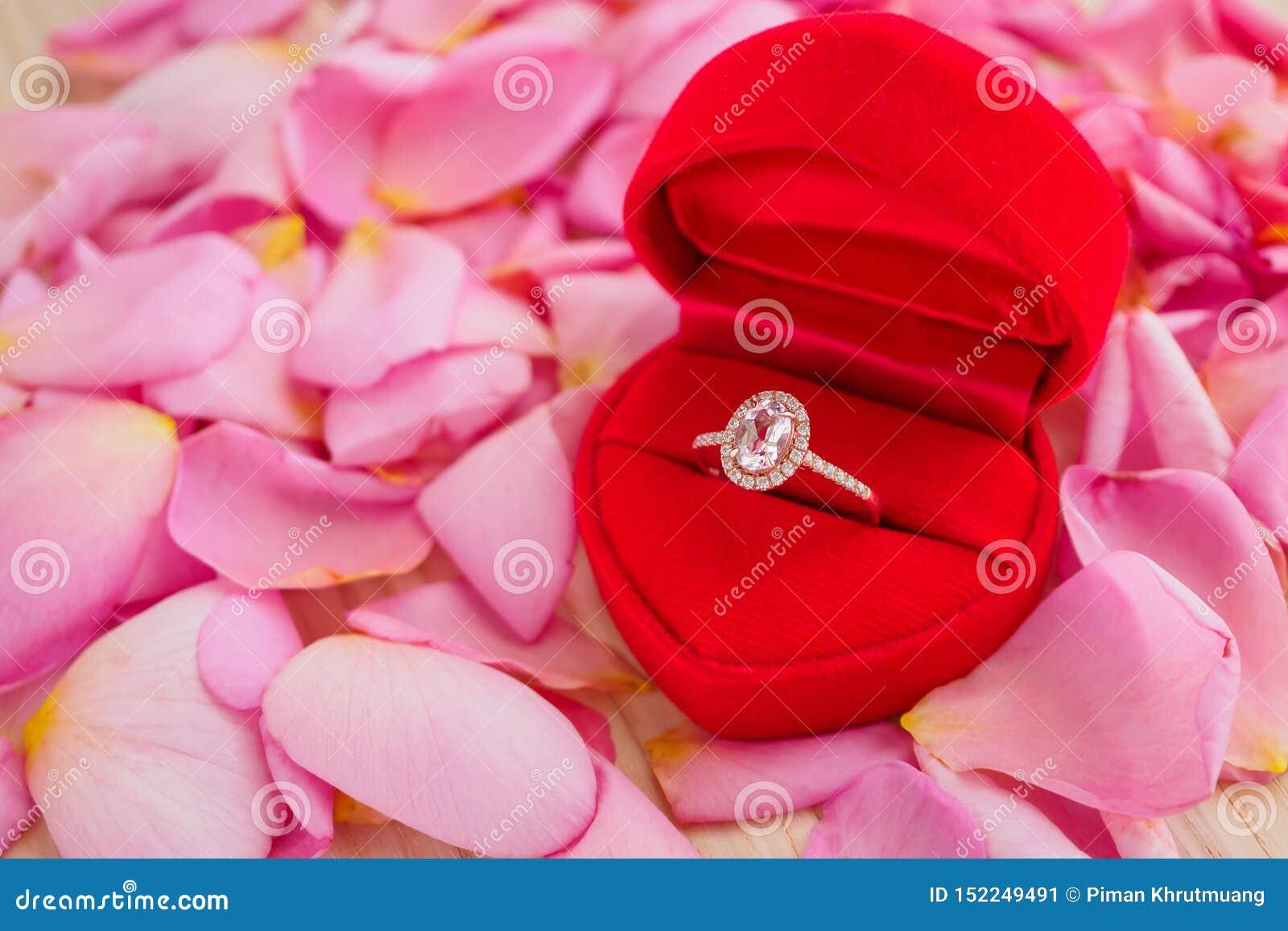 Элегантное кольцо с бриллиантом свадьбы в шкатулке для драгоценностей сердца на красивой розовой предпосылке лепестка розы