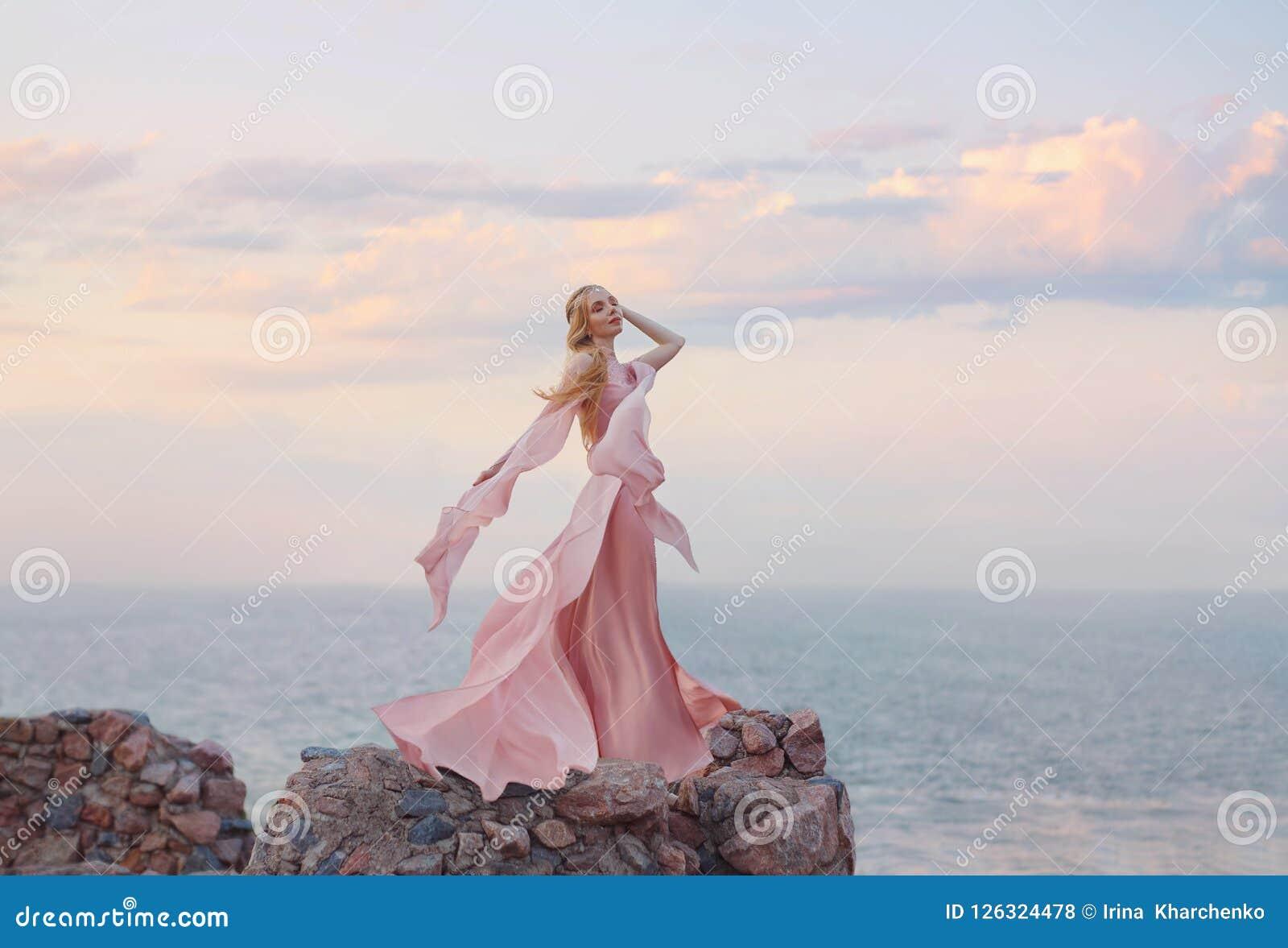 Элегантный эльф девушки с белокурыми справедливыми волнистыми волосами с тиарой на ей, носящ длинный свет - платье розы пинка roz