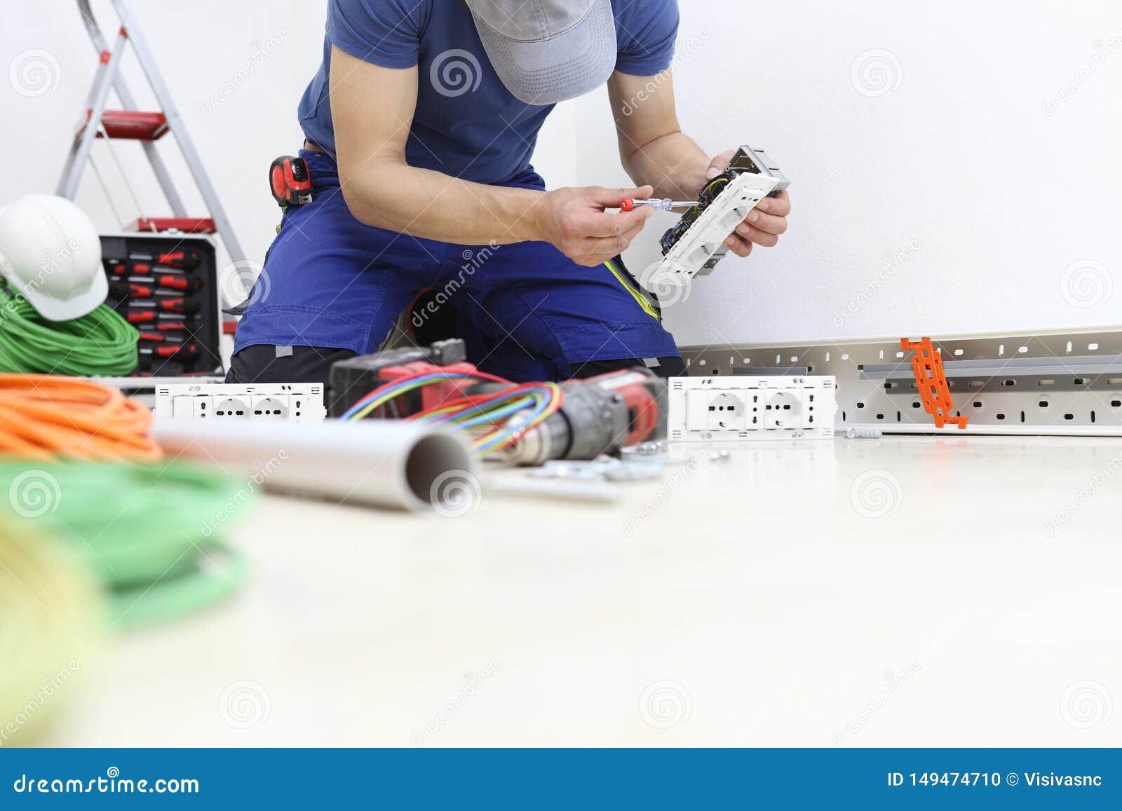 Электрик на работе с отверткой в руке соединяет кабели с гнездом для электрической проводки