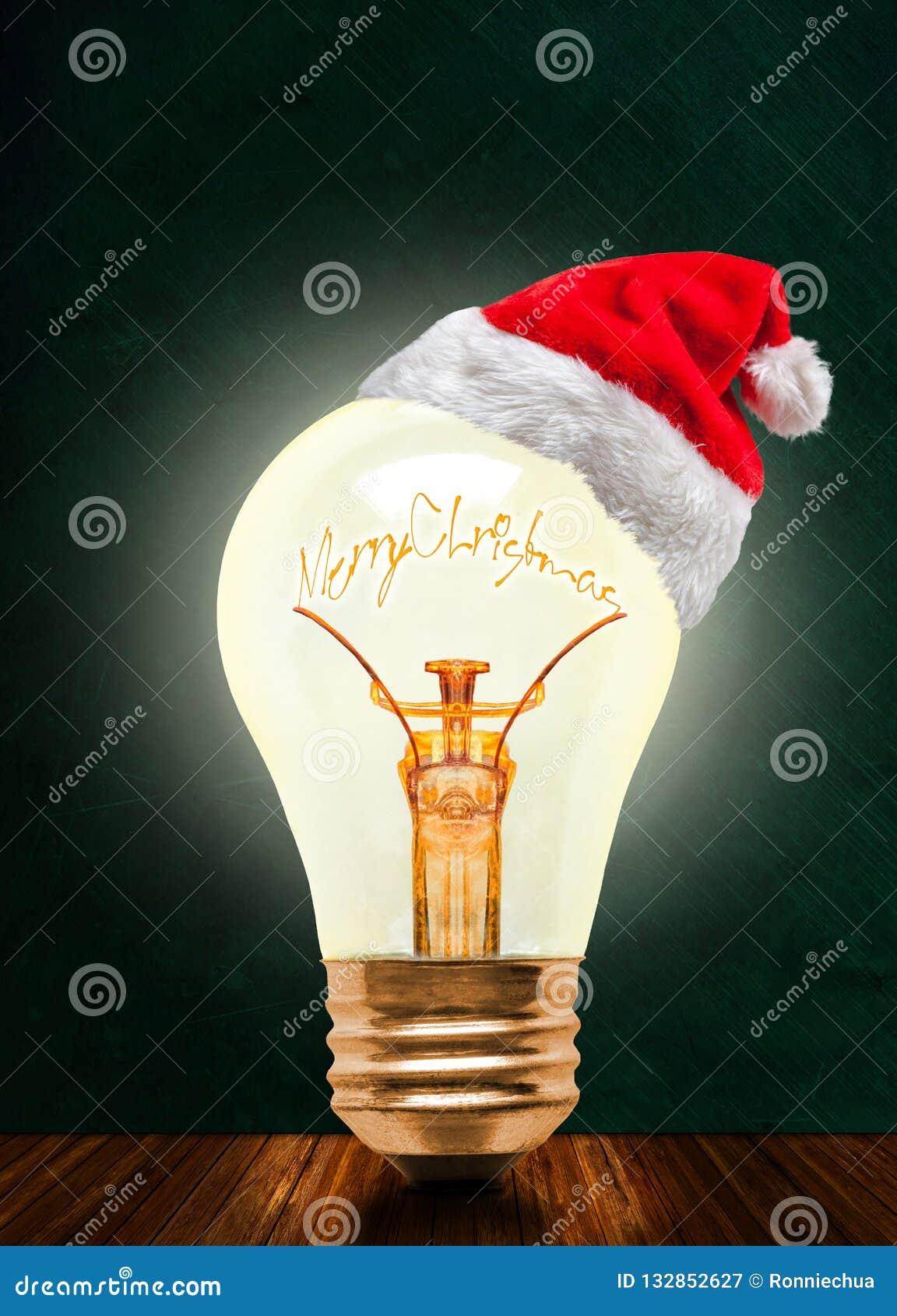 Электрическая лампочка веселого рождества накаляя со шляпой Санта и космосом экземпляра