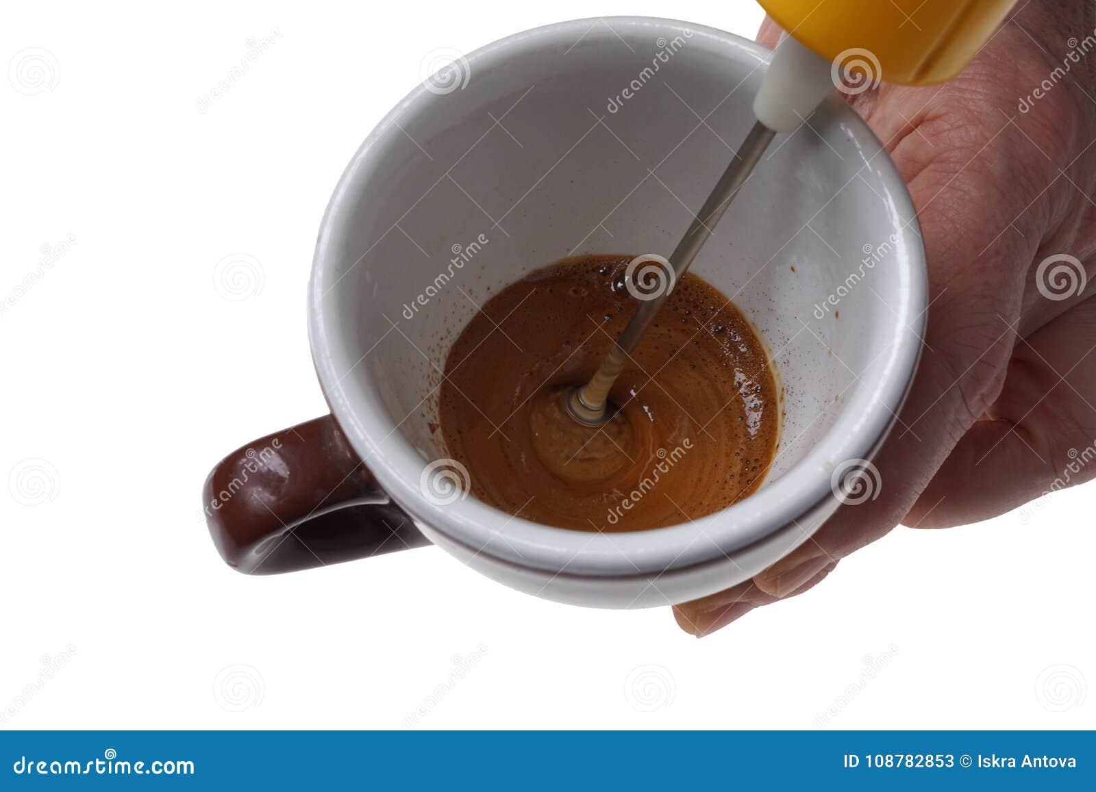 Электрический загонщик для растворимого кофе и чашки изолированных на белизне