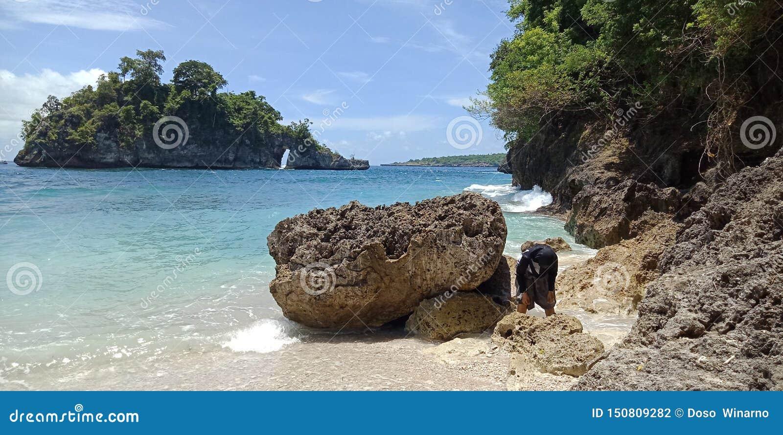 Этот пляж Canggu каменный, путешественник не только может видеть существование уникального виска также имеет склоняя область кото