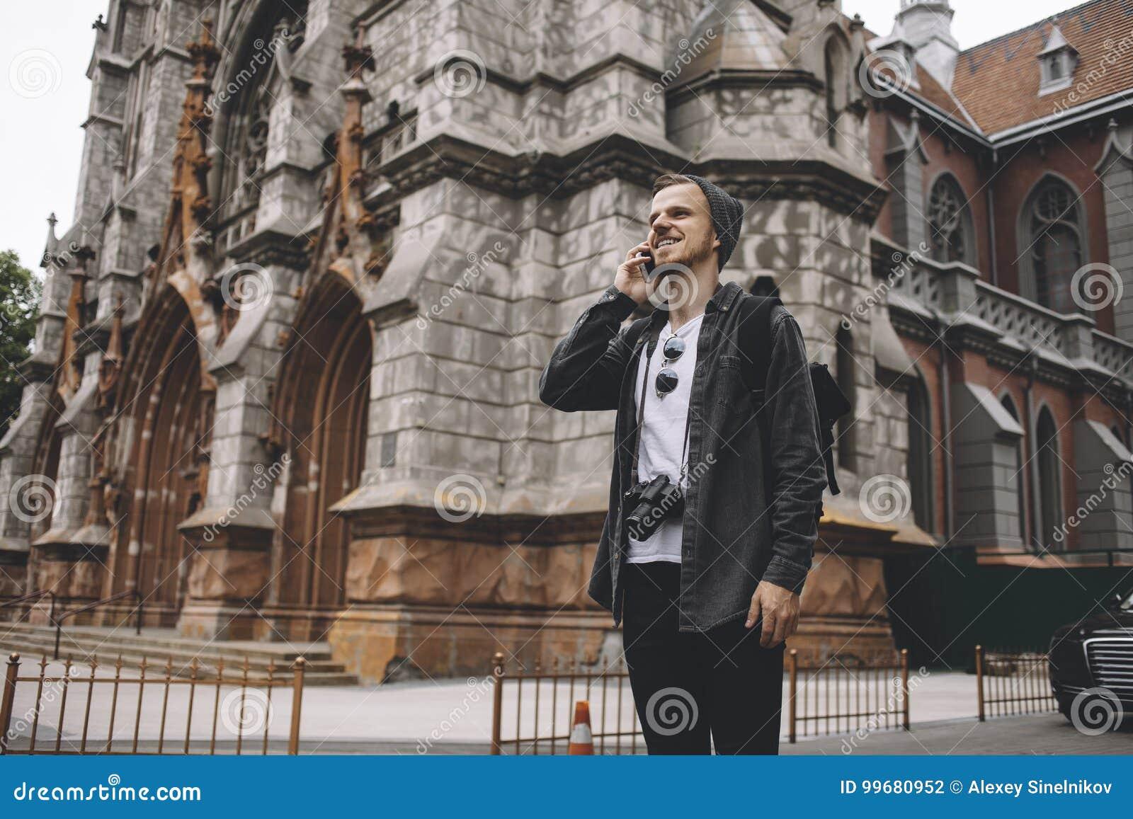 Этот турист стоит на дороге около старого коричневого здания Он говорит на телефоне и усмехается с жизнерадостным