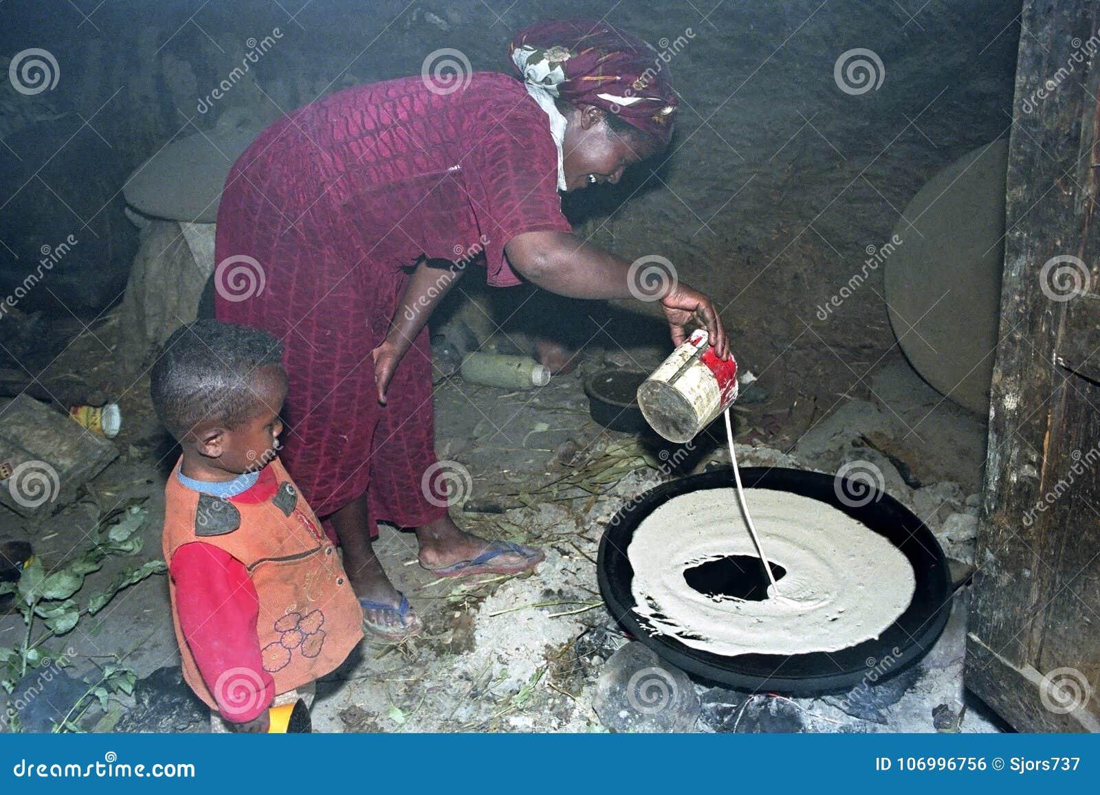 Эфиопская женщина с сыном печет injera на деревянном огне
