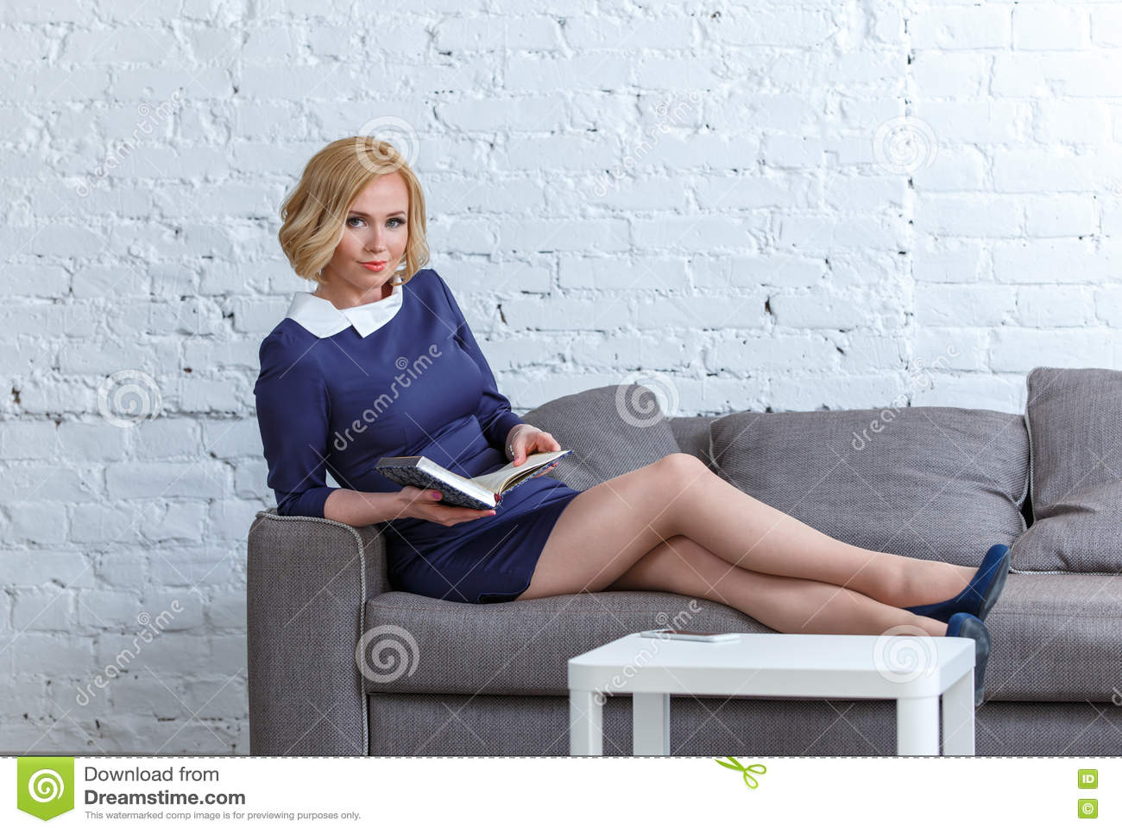 Элегантная молодая женщина лежа на удобной софе с ее дневником