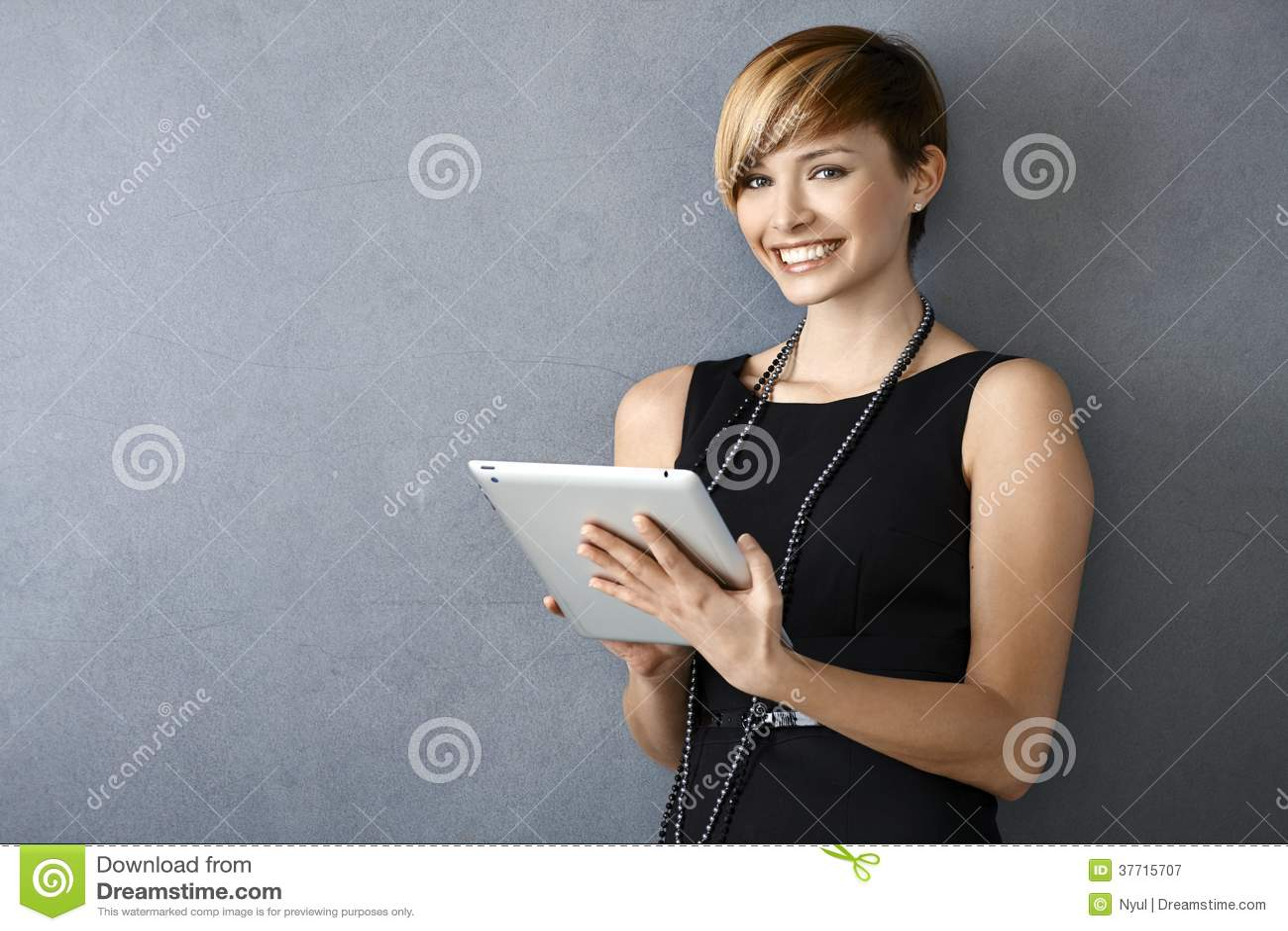 Элегантная молодая женщина используя таблетку полагаясь к стене