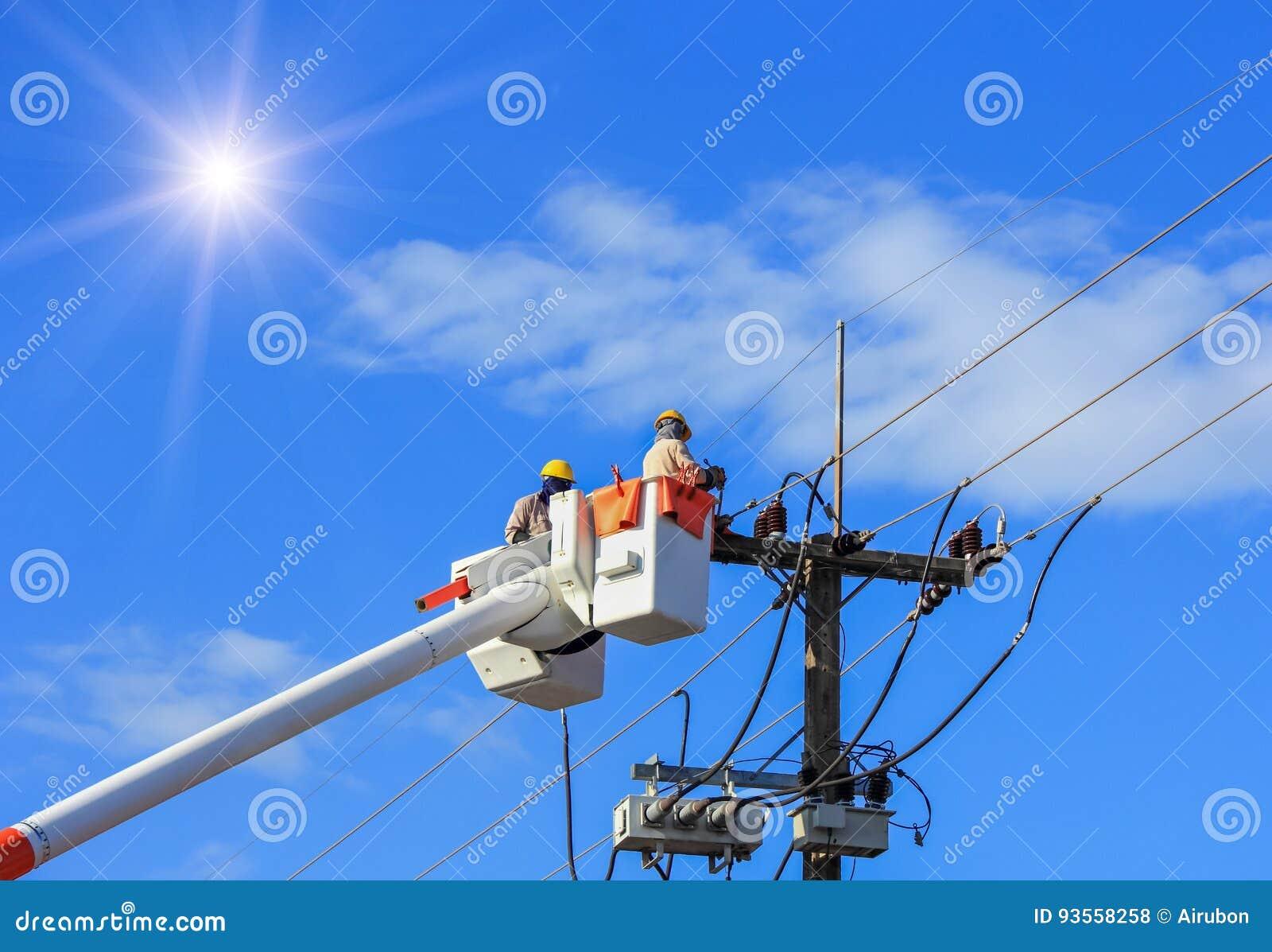 Электрики ремонтируя провод линии электропередач с платформой ведра гидравлической поднимаясь