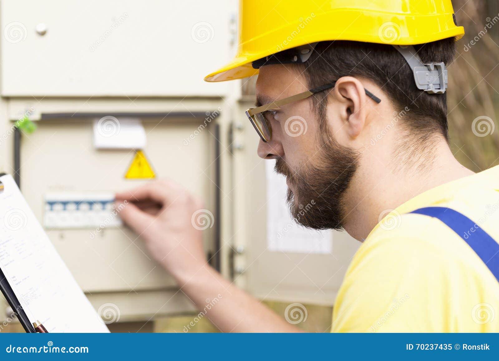 Электрик проверяя коробку взрывателя