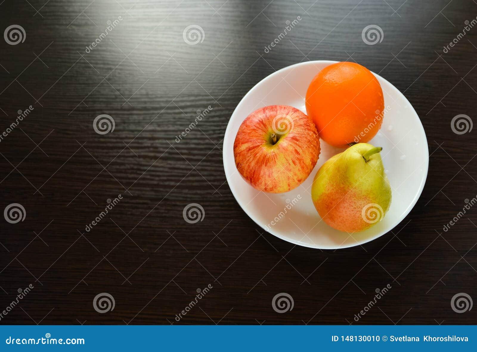 Яблоко, груша, оранжевая ложь на белой плите