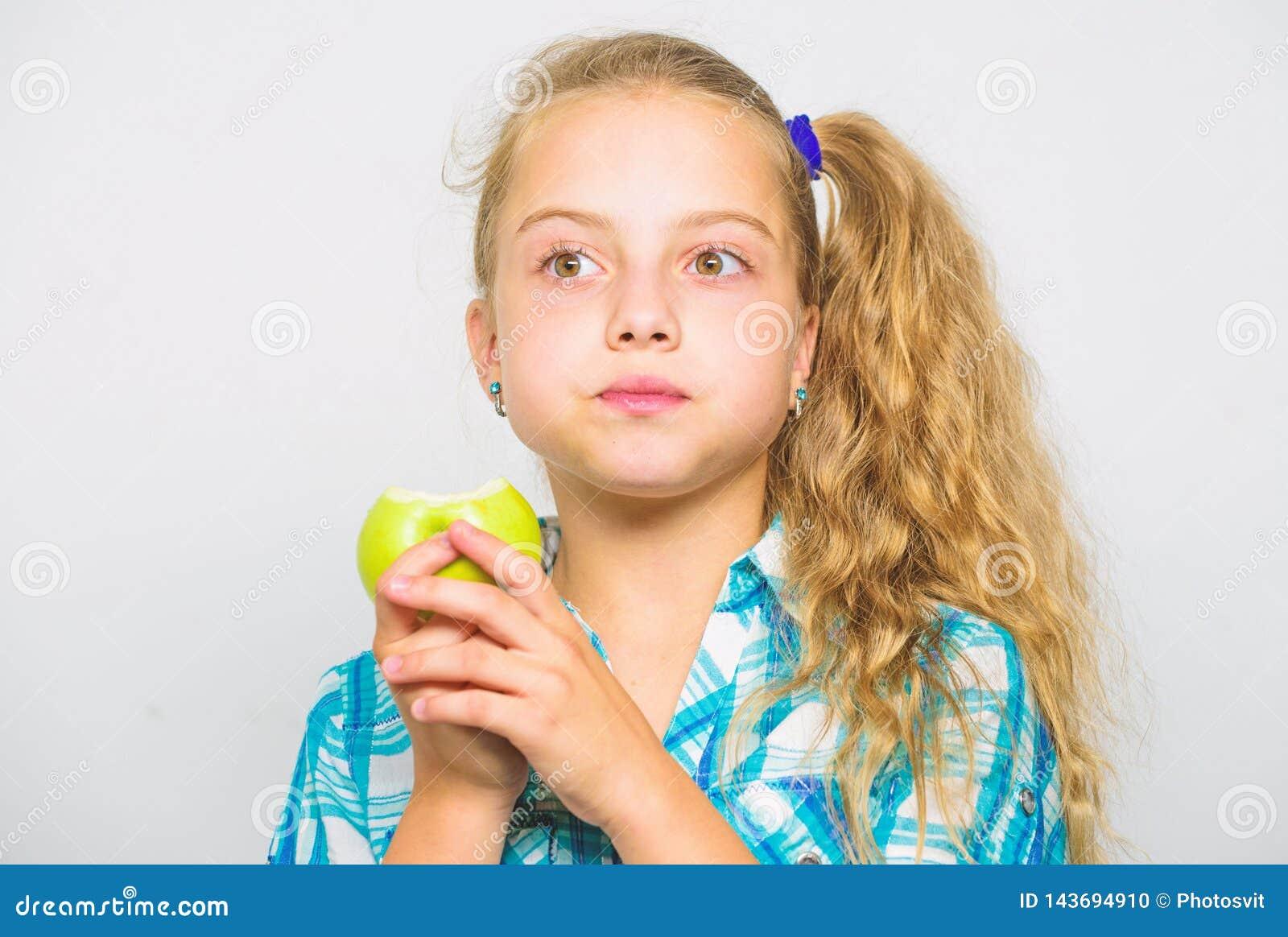 Яблоко день держит доктора отсутствующий Хорошее питание необходимо к хорошим здоровьям Девушка ребенк ест зеленый плодоовощ ябло
