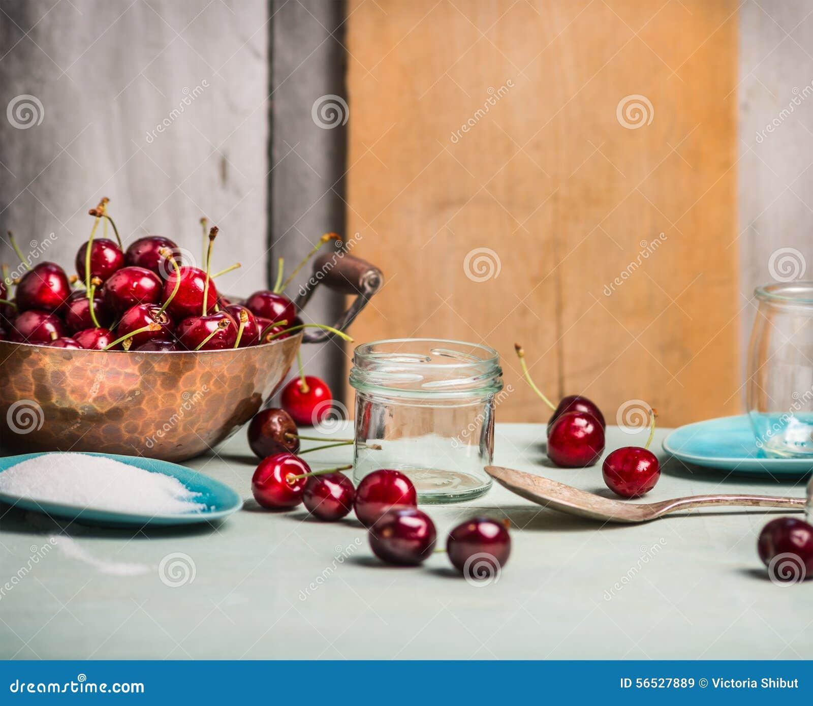 Ягоды вишен сохраняя с стеклянным опарником на деревенском кухонном столе