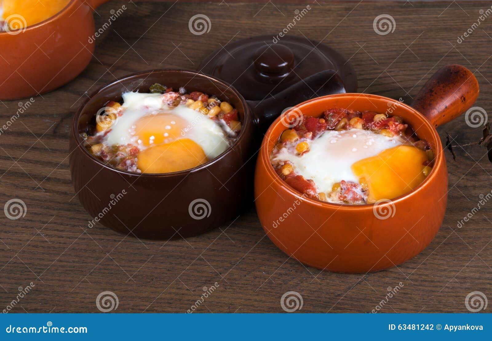 Яичка испекли с сметанообразными соусом, мозолью, ветчиной, сыром и травами в cera
