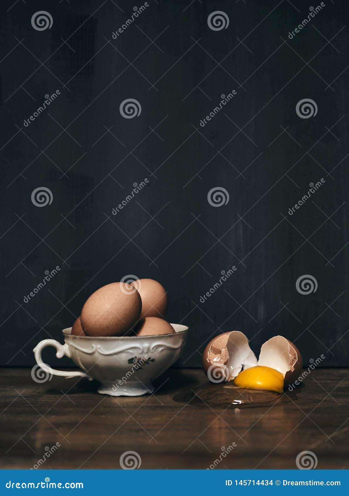 Яйца в чашке porcelaine с треснутым яйцом рядом с на винтажной таблице