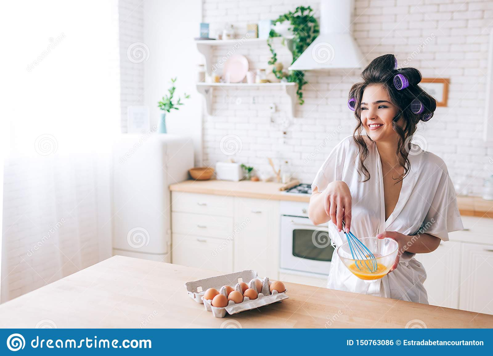 Яйца красивой жизнерадостной славной молодой домохозяйки смешивая в кухне Смотреть, который нужно встать на сторону и усмехнуться