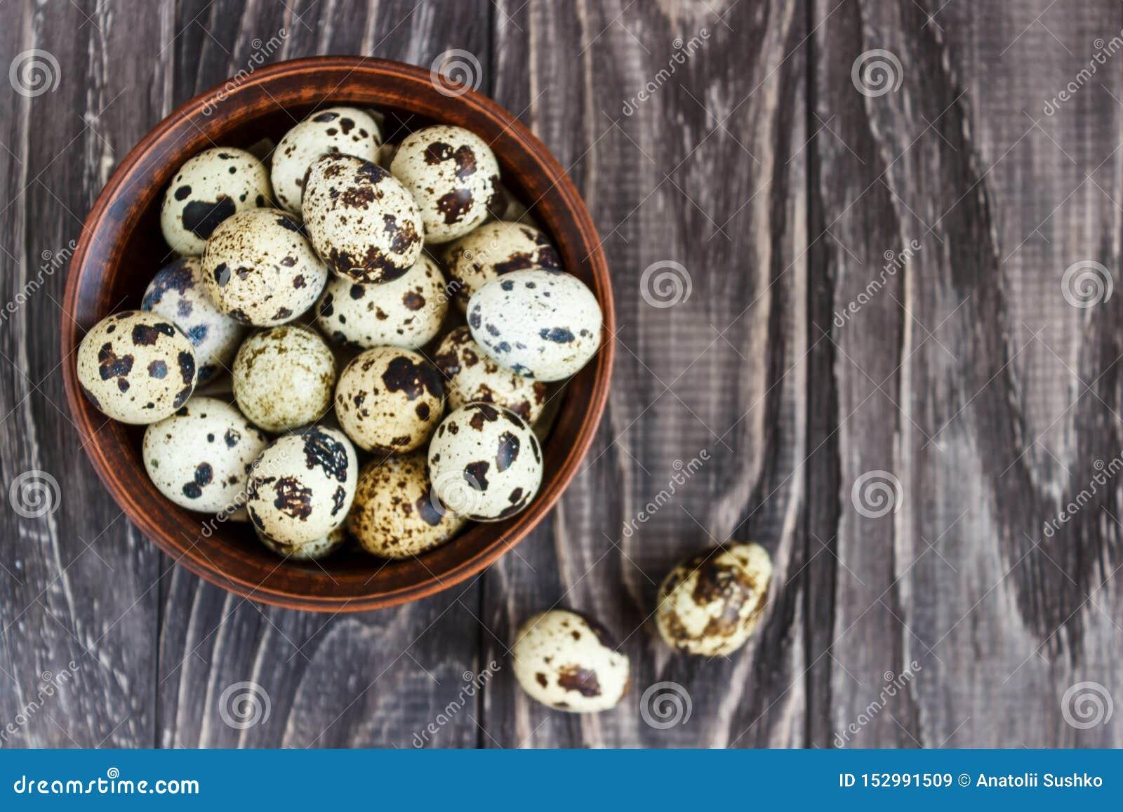 Яйца триперсток в плите глины на деревянной предпосылке, плите для хранить яйца триперсток, символ сезона пасхи r