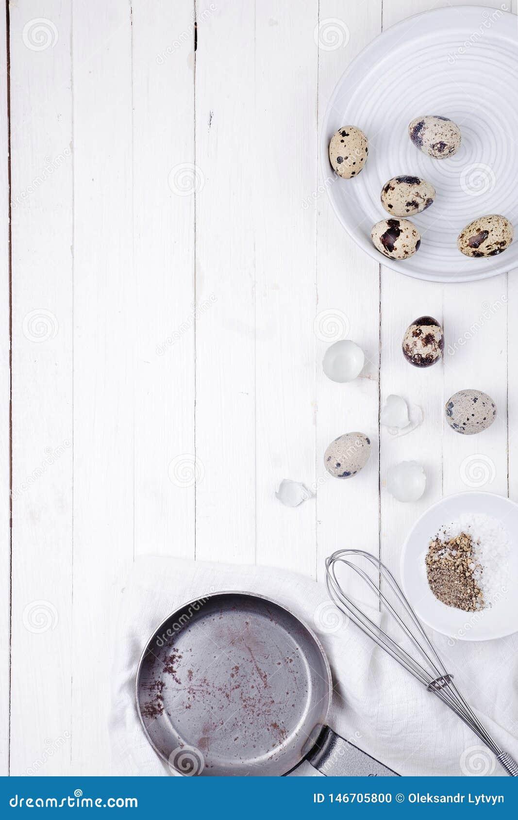 Яйца триперсток в плите, раковине, венчике для бить и сковороде на белой деревянной предпосылке r