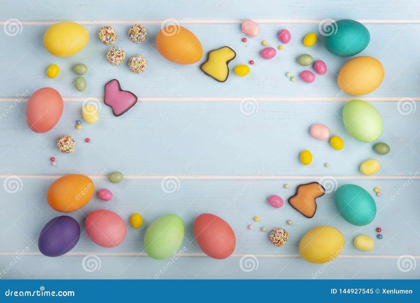 Яйца цыпленка пасхи красочные, зайчики шоколада, разнообразие помадок