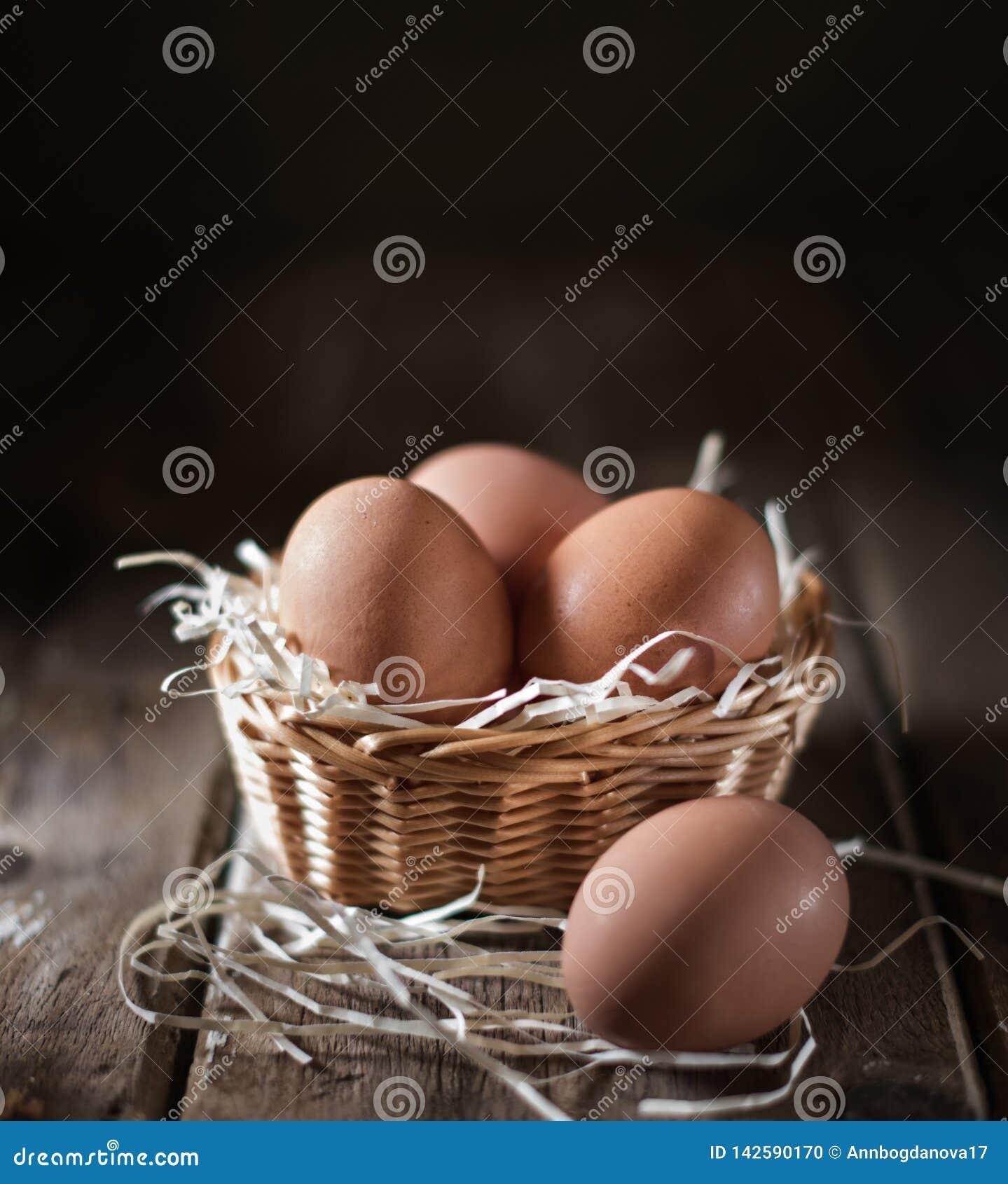Яйцо в плетеной корзине на деревенской таблице