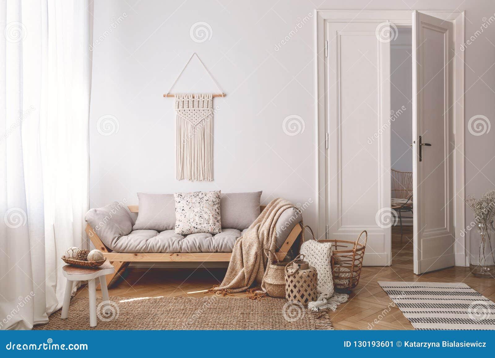 Яркая живущая комната внутренняя с уникальными, handmade корзинами сделала из естественных материалов и уютной деревянной софы с